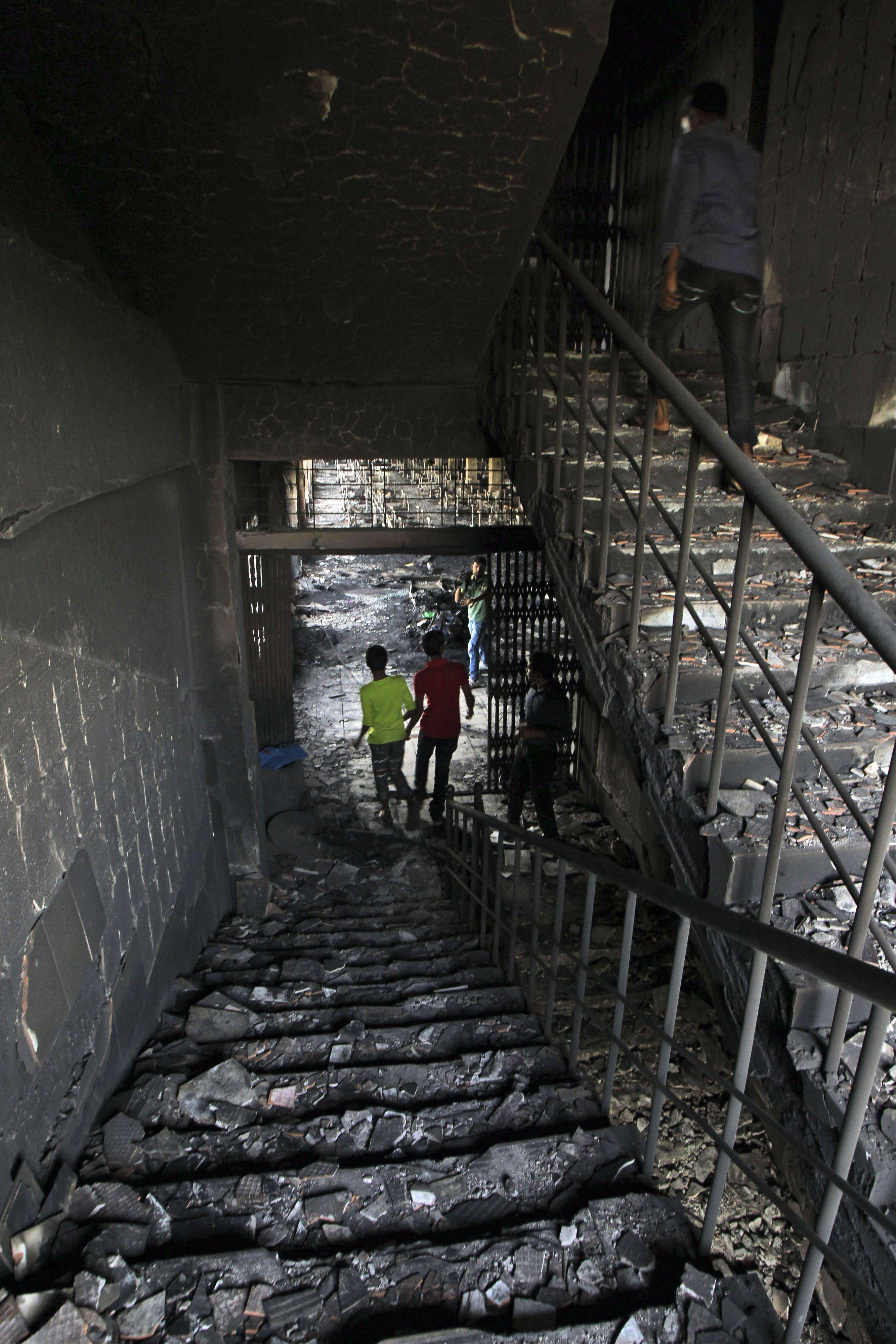 "People walk inside a garment-factory where a fire killed 112 people on the outskirts of Dhaka, Bangladesh. About a year before the fire, executives from Wal-Mart, Gap and other big clothing companies met nearby in the country's capital to discuss a legally binding contract that would govern safety inspections. But after a spokeswoman for Wal-Mart, the world's largest retailer, got up and said the proposal wasn't ""financially feasible,"" the effort quickly lost momentum."