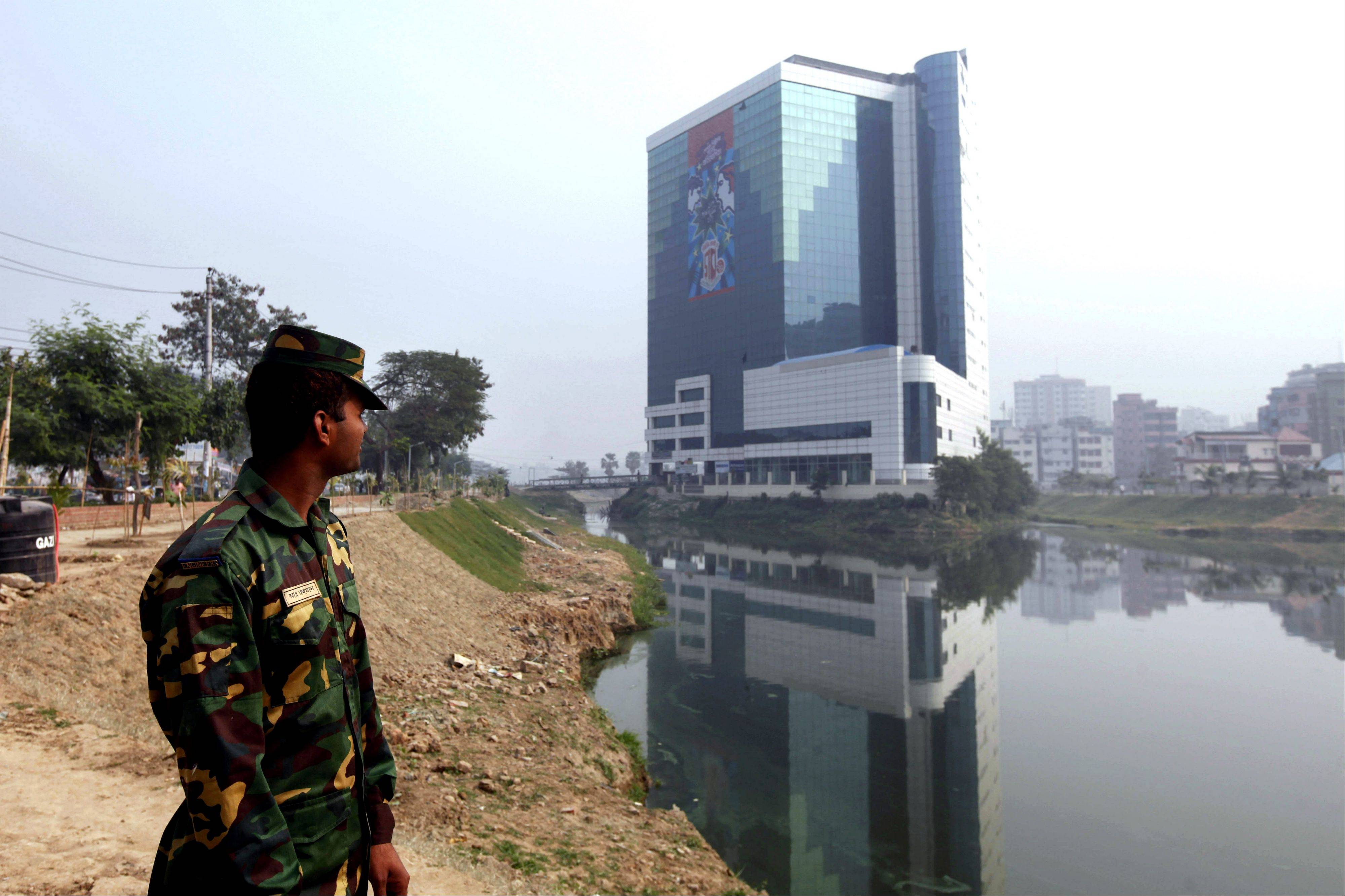 A Bangladesh Army soldier stands near the headquarters of the Bangladesh Garment Manufacturers and Export Association (BGMEA) in Dhaka, Bangladesh.