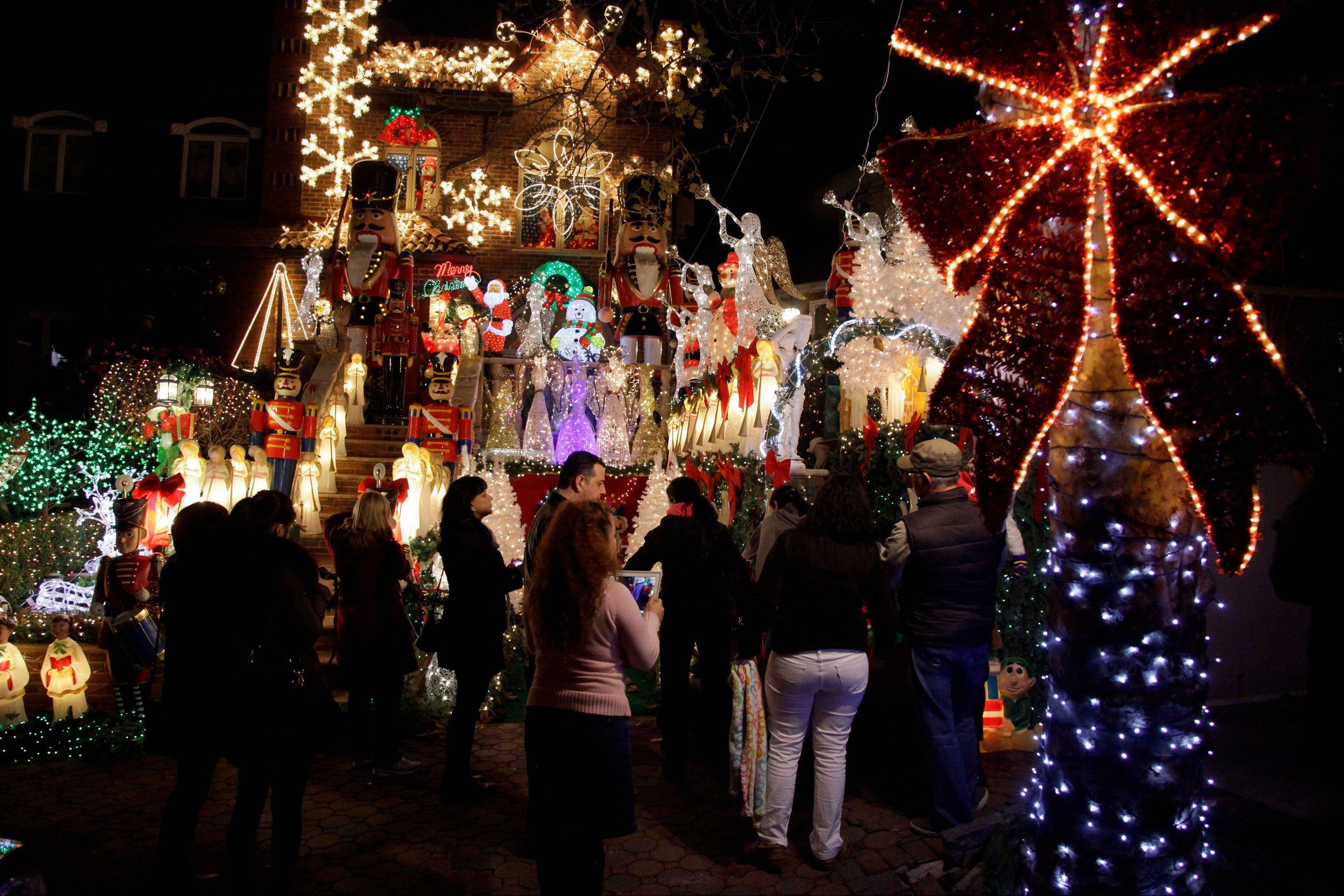 Spectators viewing an elaborately decorated home belonging to Lucy Spata as part of the Christmas Lights & Cannoli Tour of the Brooklyn neighborhoods of Dyker Heights and Bay Ridge, where locals take pride in over-the-top holiday light displays.
