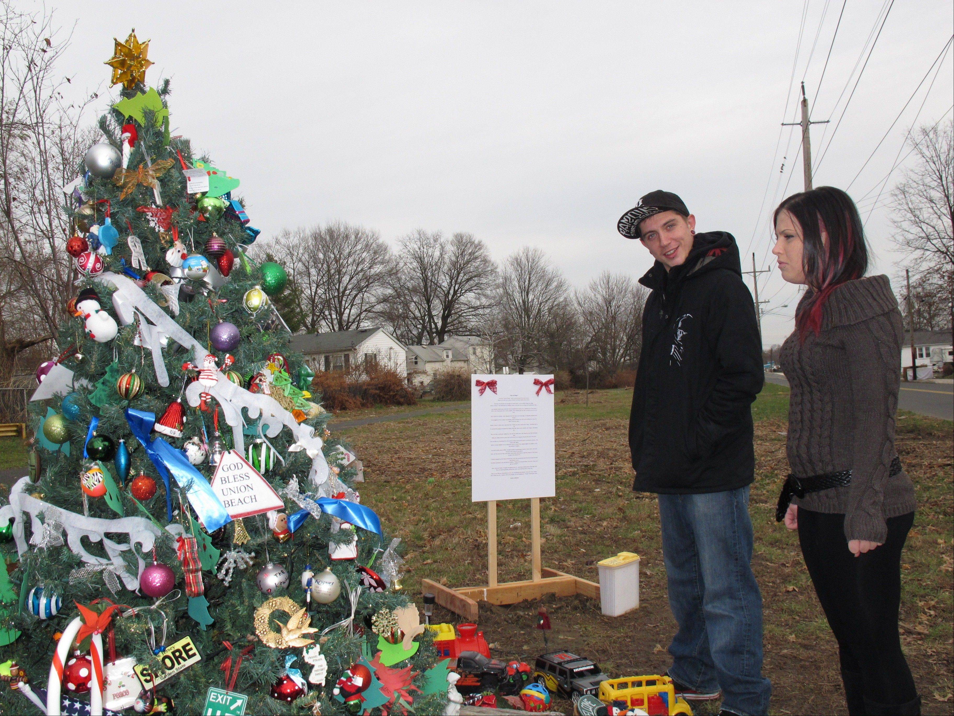 "Dan Canales, left, and Ashley Papa, right, admire the ""Tree of Hope"" in Union Beach, N.J. Canales is one of many Union Beach residents who have adopted the tree as a symbol of hope amid the devastation of Superstorm Sandy."