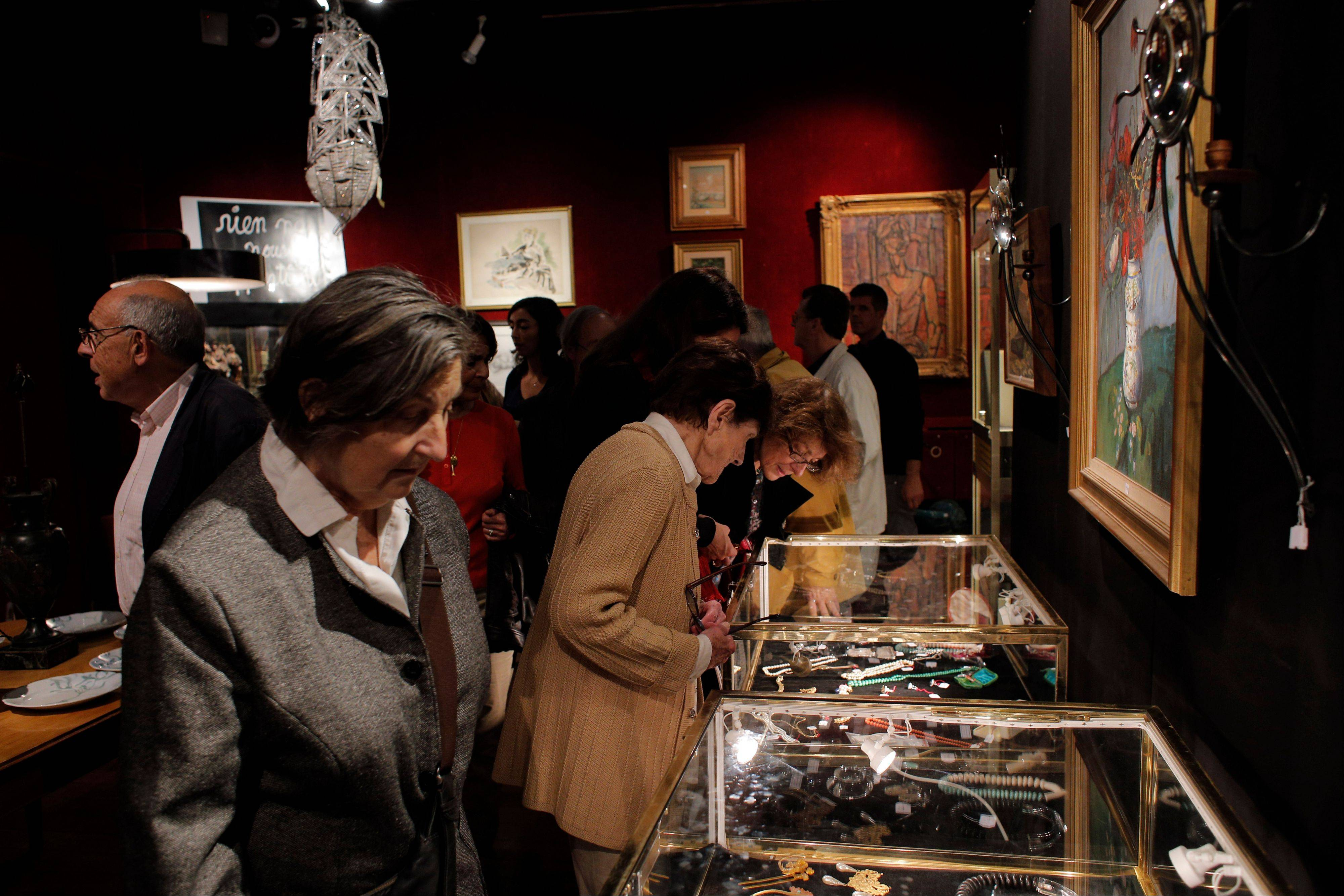 Visitors inspect jewels and paintings at the Drouot auction's house in Paris.