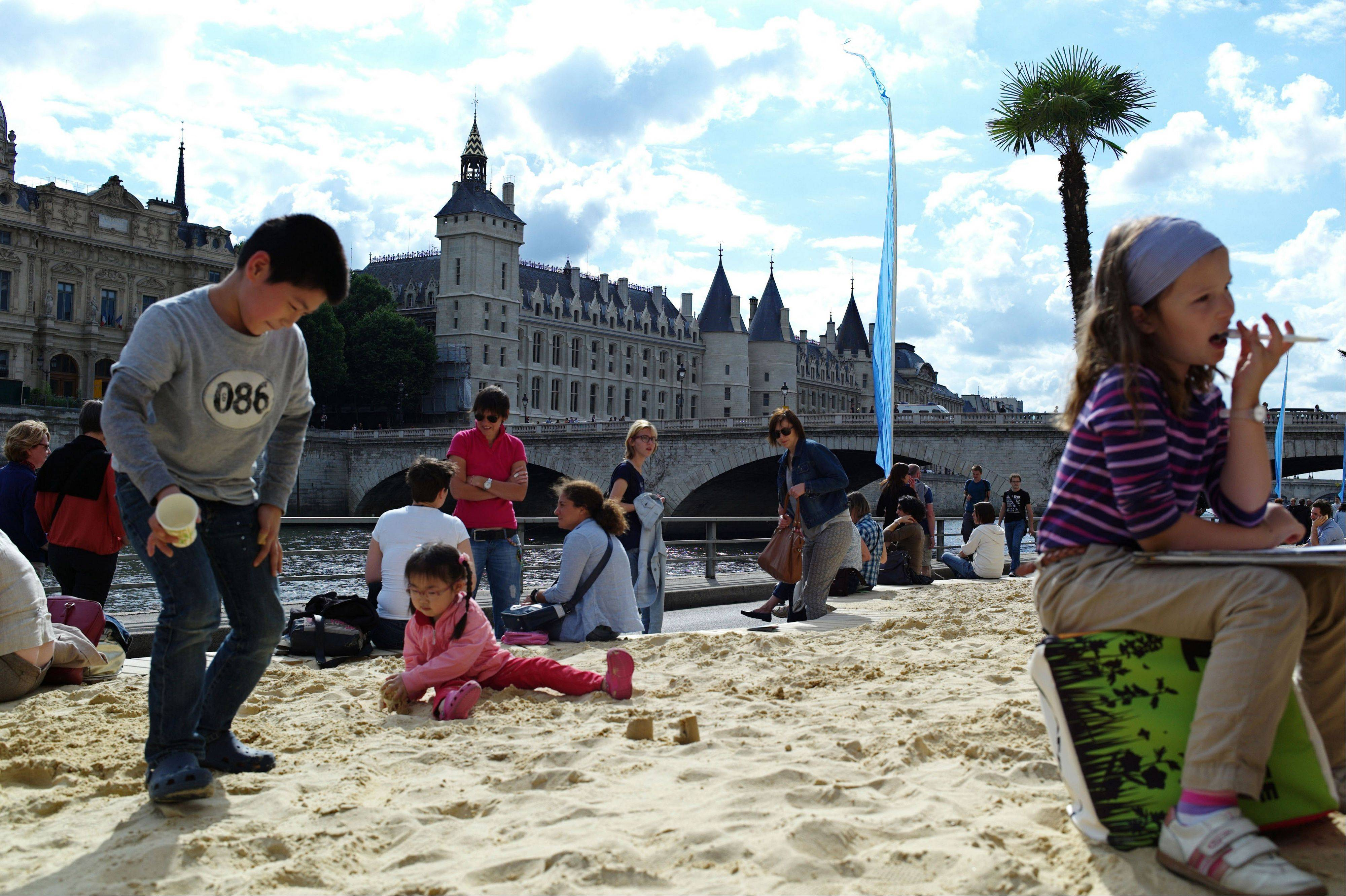 Children play in the sand during the Paris Plages event in Paris, featuring palm trees, sand beaches, hammocks, lounge chairs, volleyball courts and a pool that will line the (2.2-mile) riverside attraction.