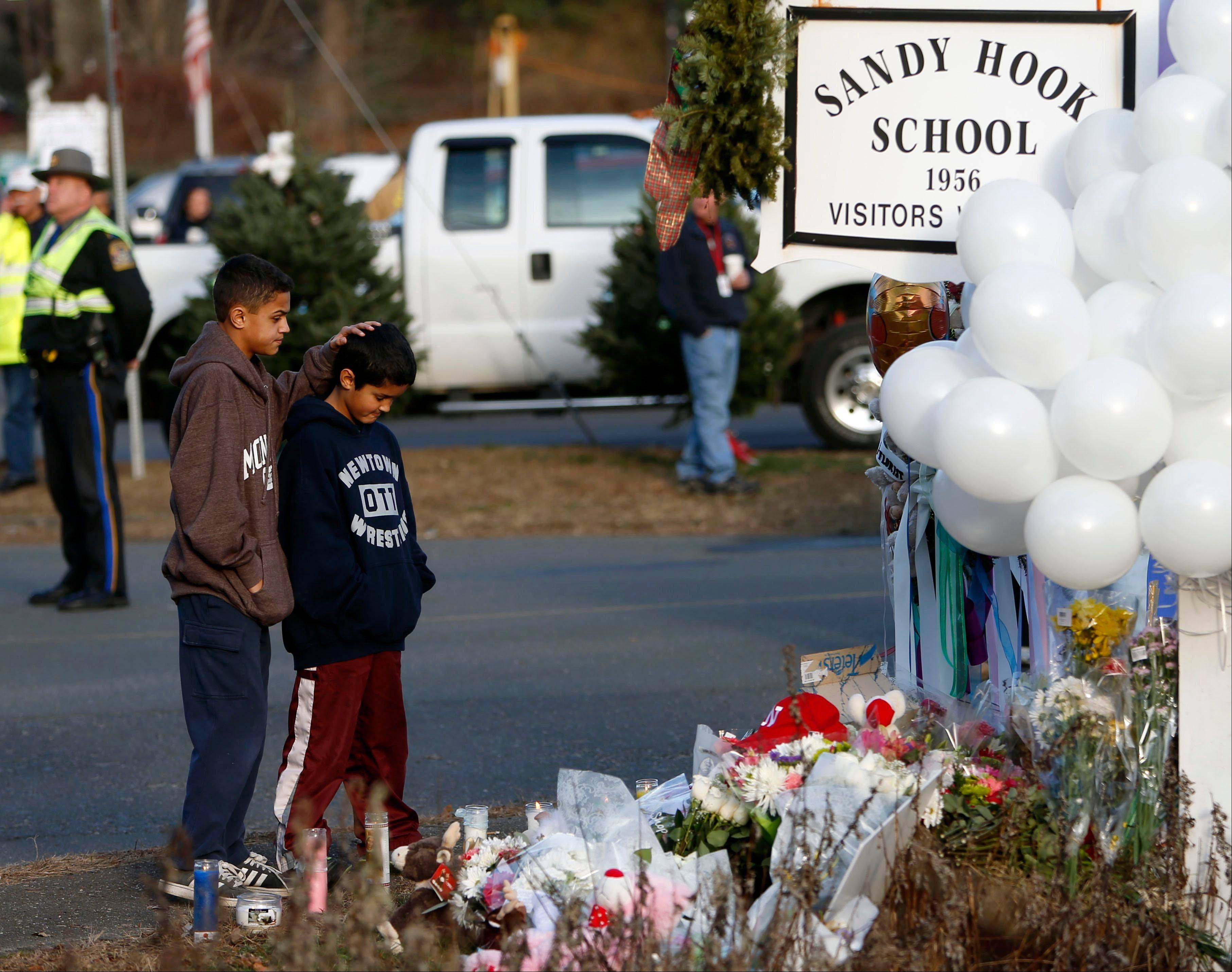 Brothers Thomas, 13, left, and Steven Leuci, 9, pay their respects at a memorial for shooting victims near Sandy Hook Elementary School in Newtown, Conn. The incident has caused schools nationwide to review their security procedures.