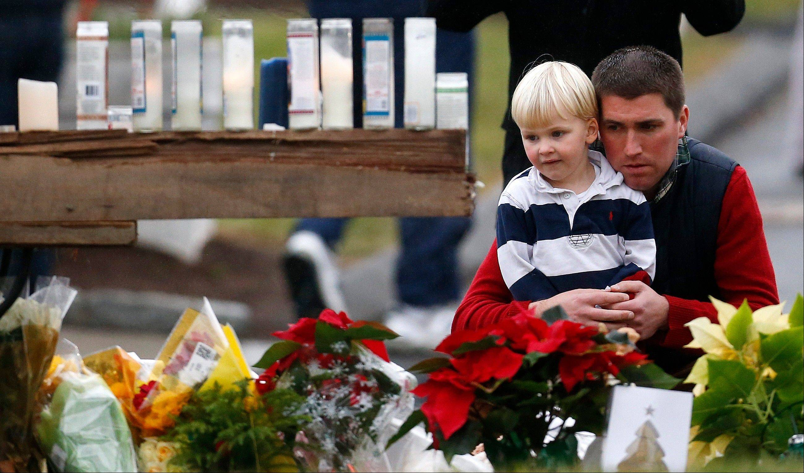 A man holds a child while paying respects to shooting victims at a makeshift memorial outside of St. Rose of Lima Roman Catholic Church, Sunday, Dec. 16, 2012, in Newtown, Conn. On Friday, a gunman killed his mother at their home and then opened fire inside the Sandy Hook Elementary School in Newtown, killing 26 people, including 20 children.