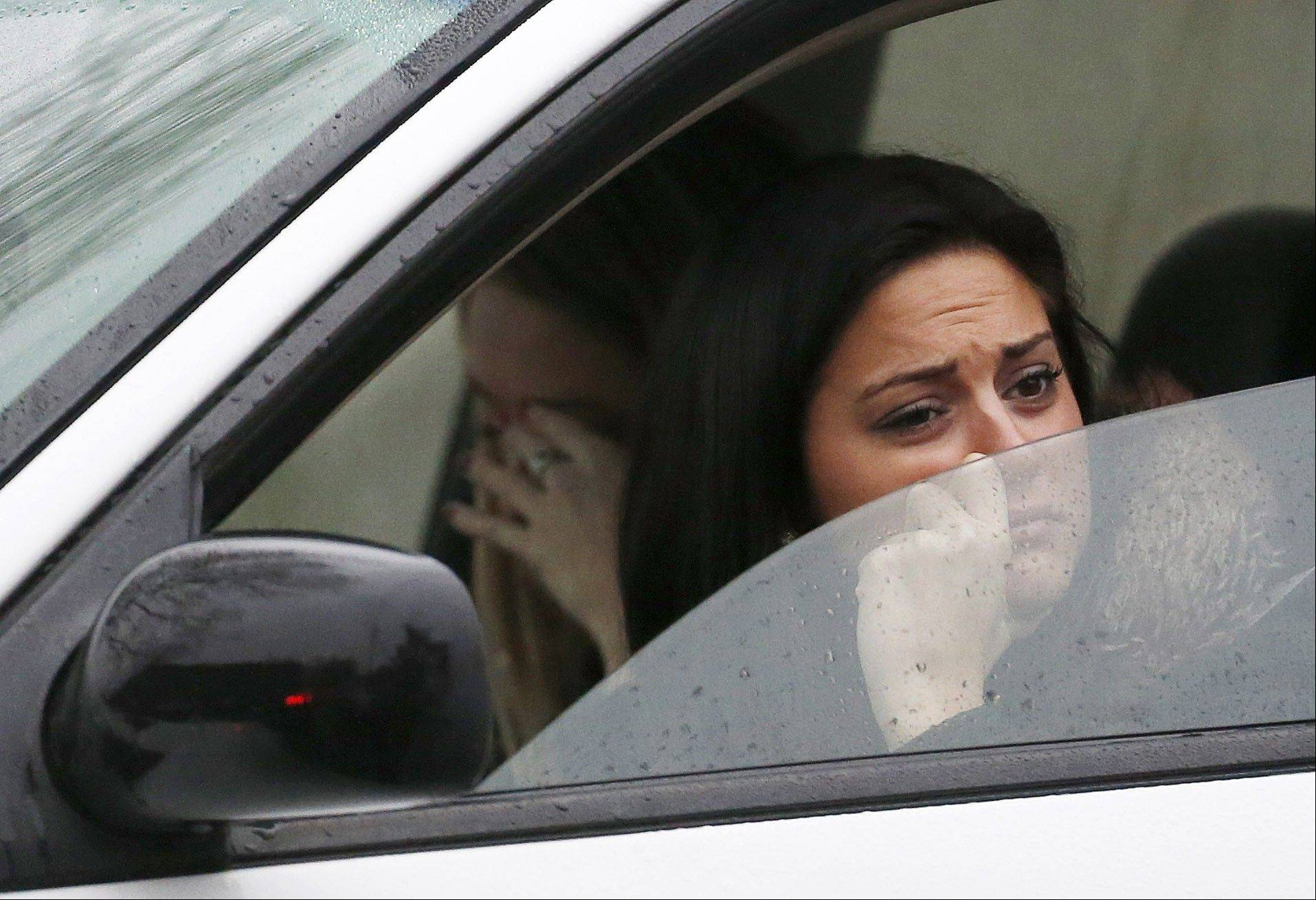 Women react while waiting in a vehicle to drive away from St. Rose of Lima Roman Catholic Church as officials respond to a bomb threat, Sunday, Dec. 16, 2012, in Newtown, Conn. Worshippers hurriedly left the church Sunday, not far from where a gunman opened fire Friday inside the Sandy Hook Elementary School in Newtown.