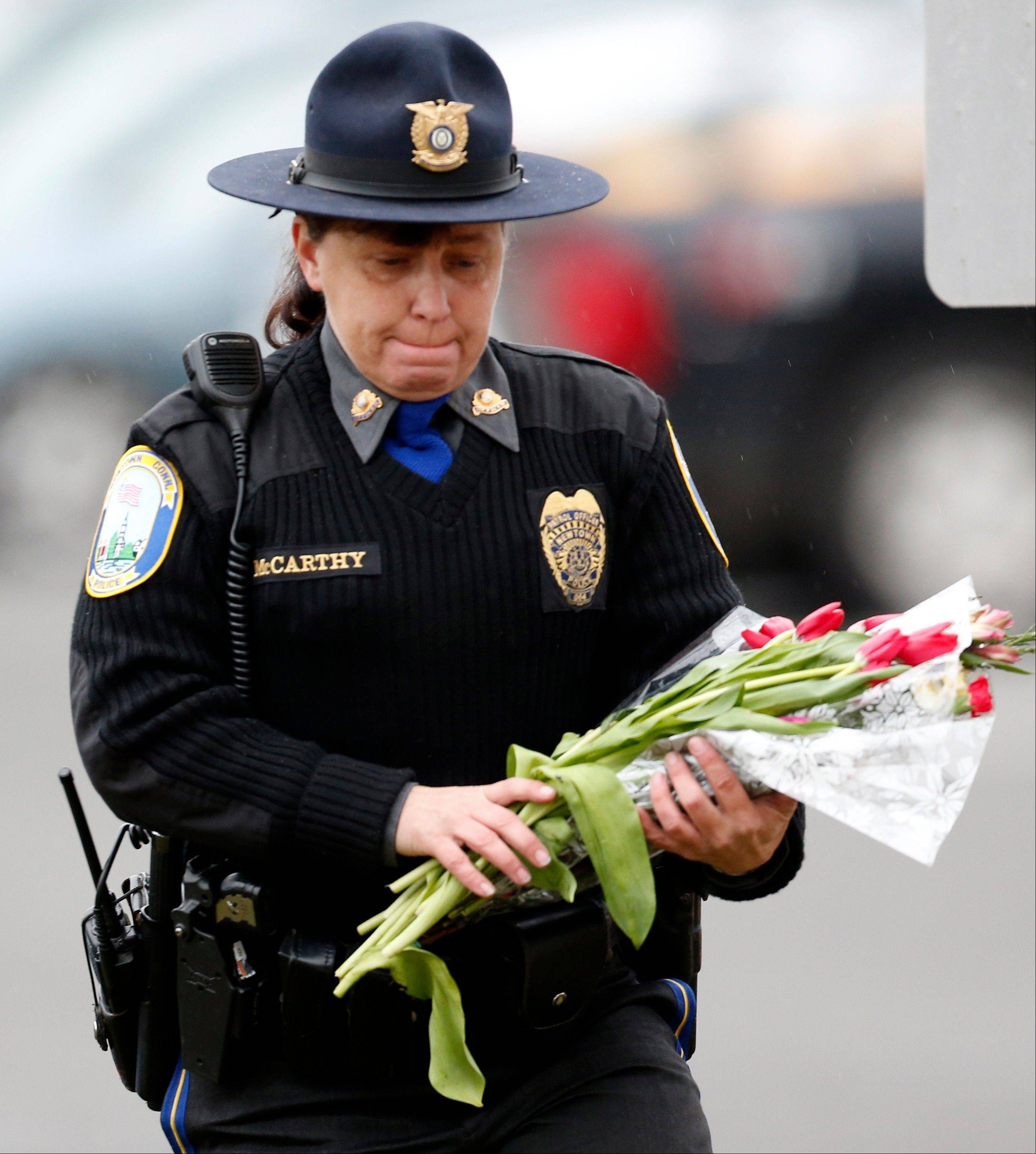 Newtown Police Officer Maryhelen McCarthy places flowers at a makeshift memorial outside St. Rose of Lima Roman Catholic Church, Sunday, Dec. 16, 2012, in Newtown, Conn. On Friday, a gunman allegedly killed his mother at their home and then opened fire inside the Sandy Hook Elementary School, killing 26 people, including 20 children.