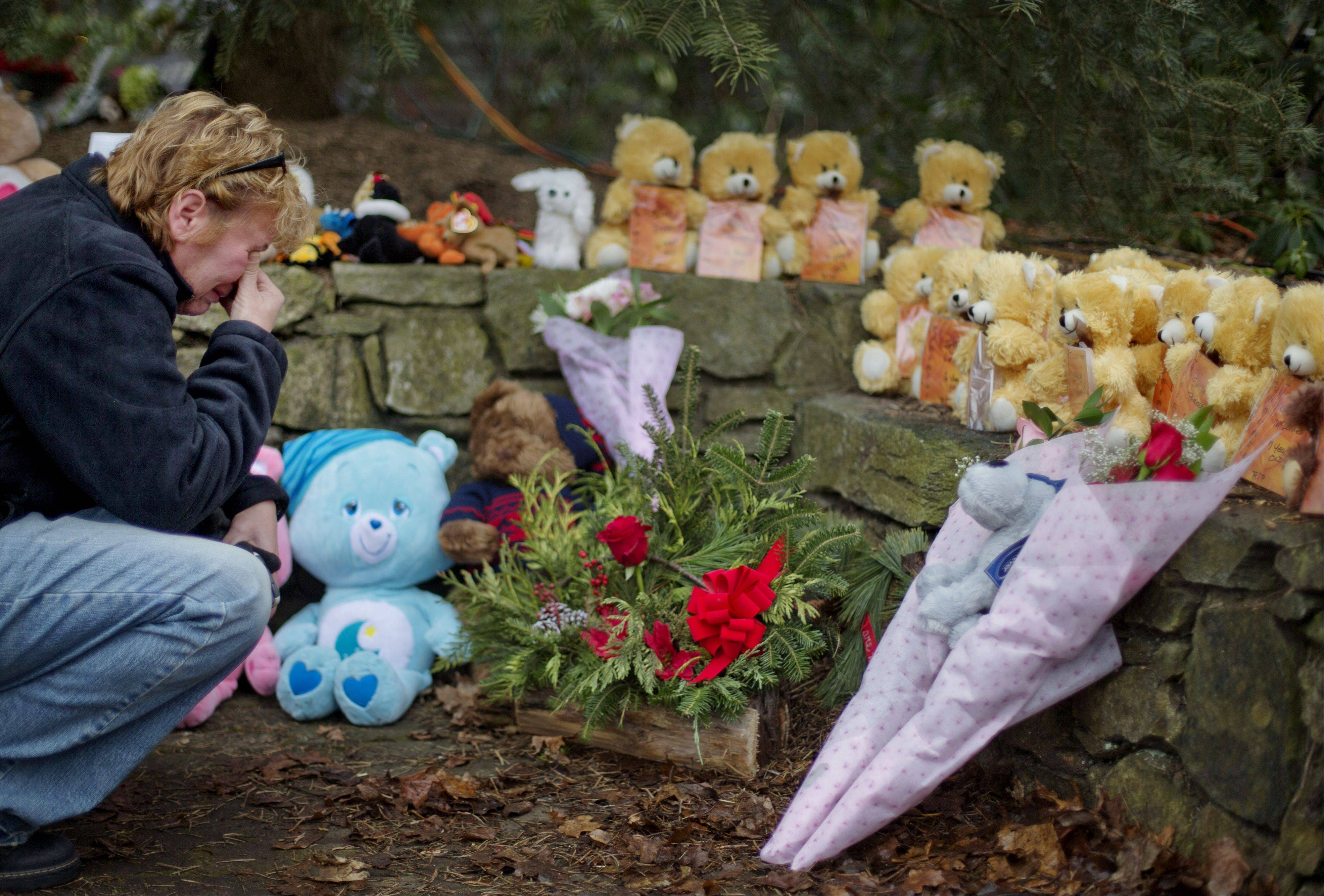 Cheryl Girardi, of Middletown, Conn., kneels beside 26 teddy bears, each representing a victim of the Sandy Hook Elementary School shooting, at a sidewalk memorial Sunday in Newtown, Conn.