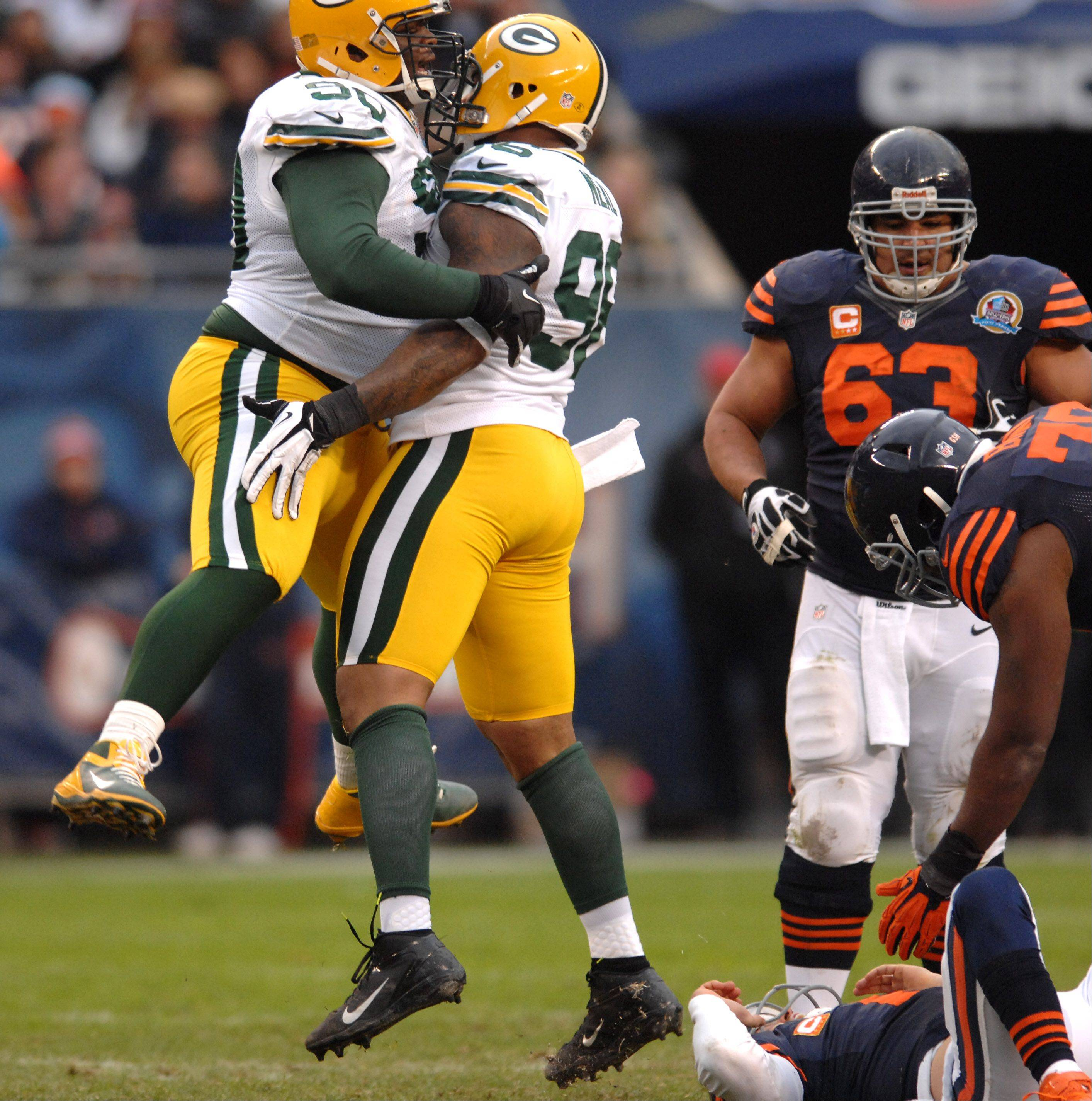 Green Bay Packers nose tackle B.J. Raji (90) and defensive tackle Jordan Miller (96) celebrate a sack of Chicago Bears quarterback Jay Cutler (6) during Sunday's game at Soldier Field in Chicago.