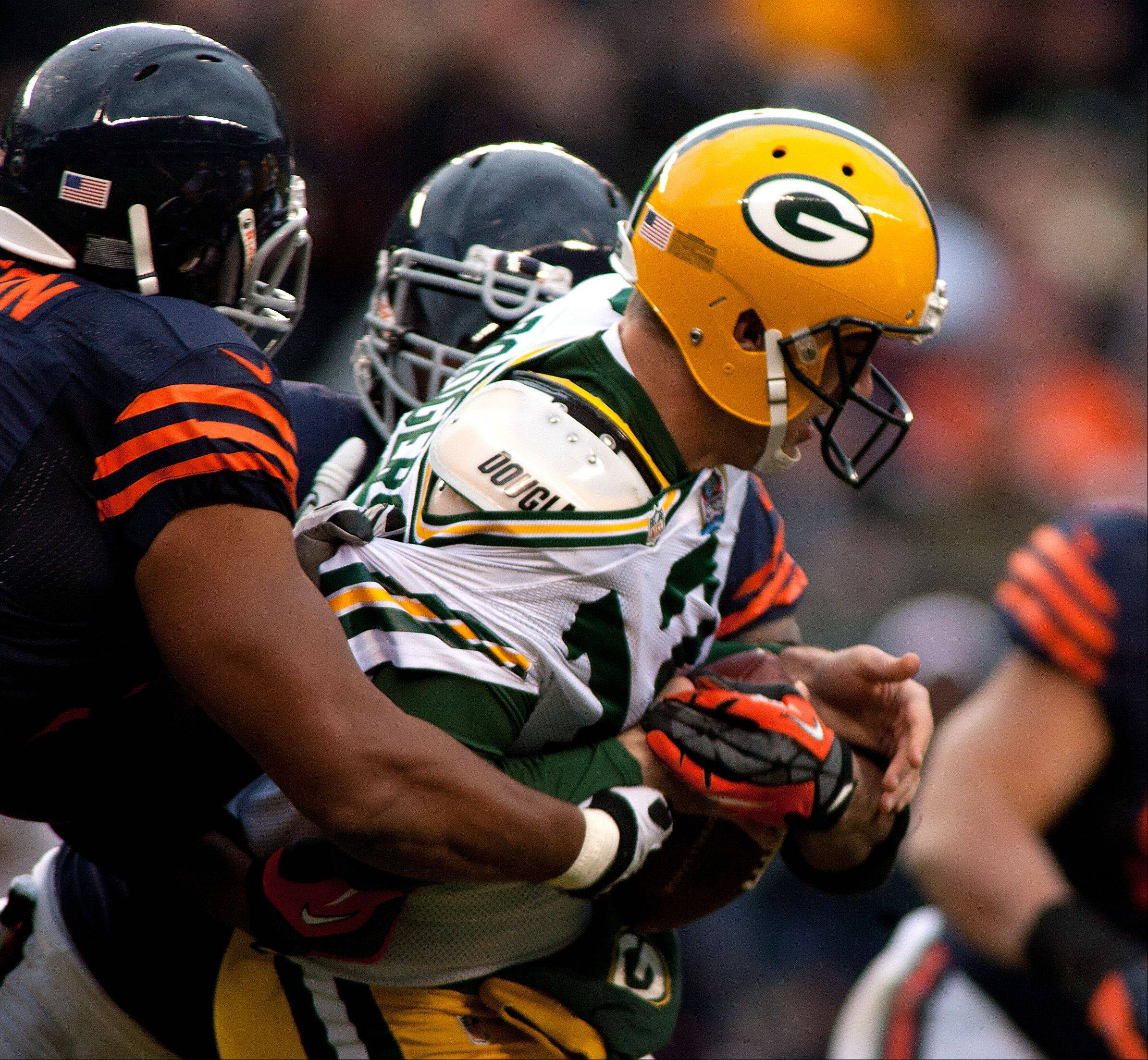 The Bear's Corey Wootton, left, sacks Packer quarterback Aaron Rodgers, during the first half of Sunday's game at Soldier Field in Chicago.