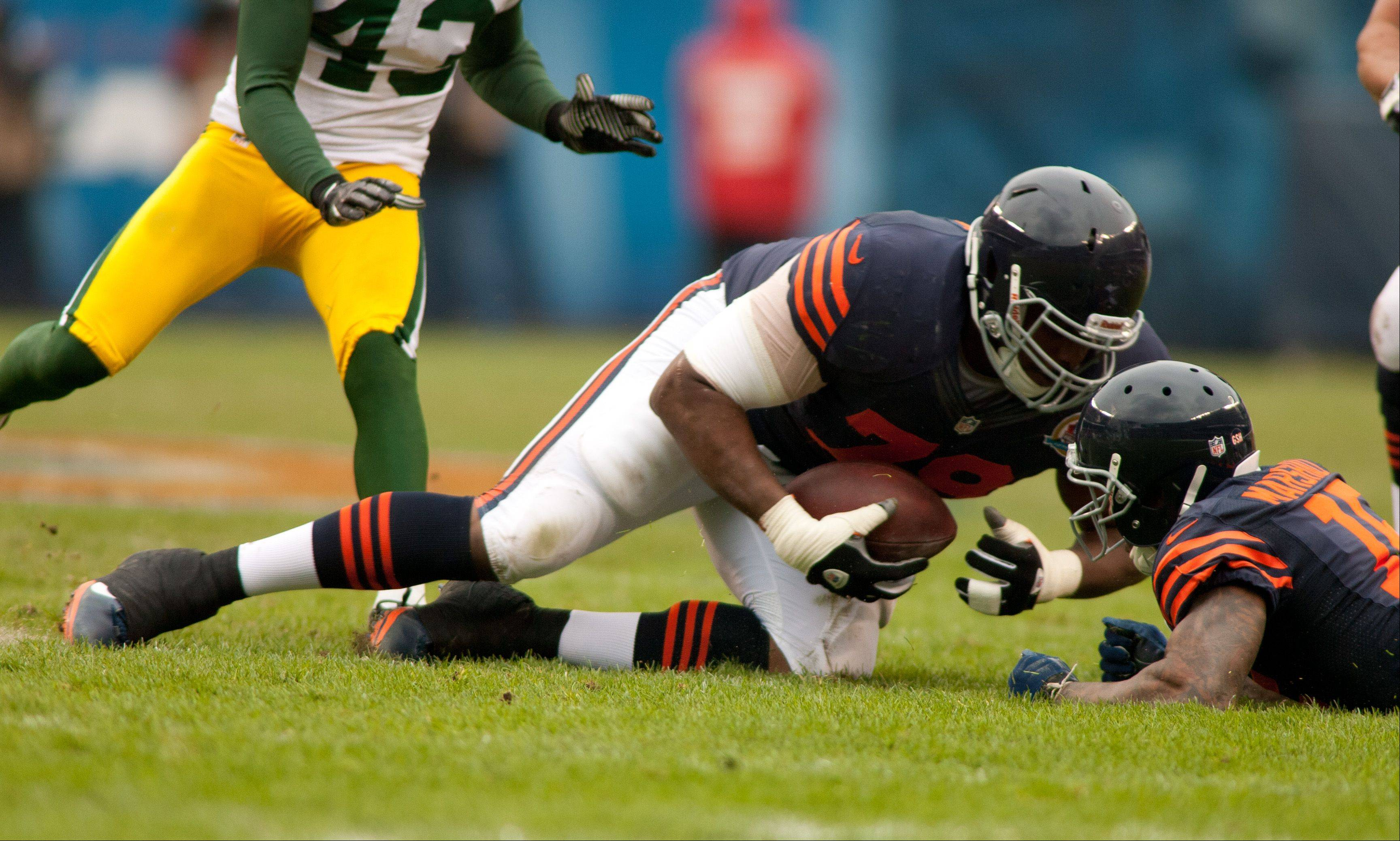 The Bears' J.T. Thomas, left, recovers a Brandon Marshall first half fumble, right, during Sunday's game at Soldier Field in Chicago.