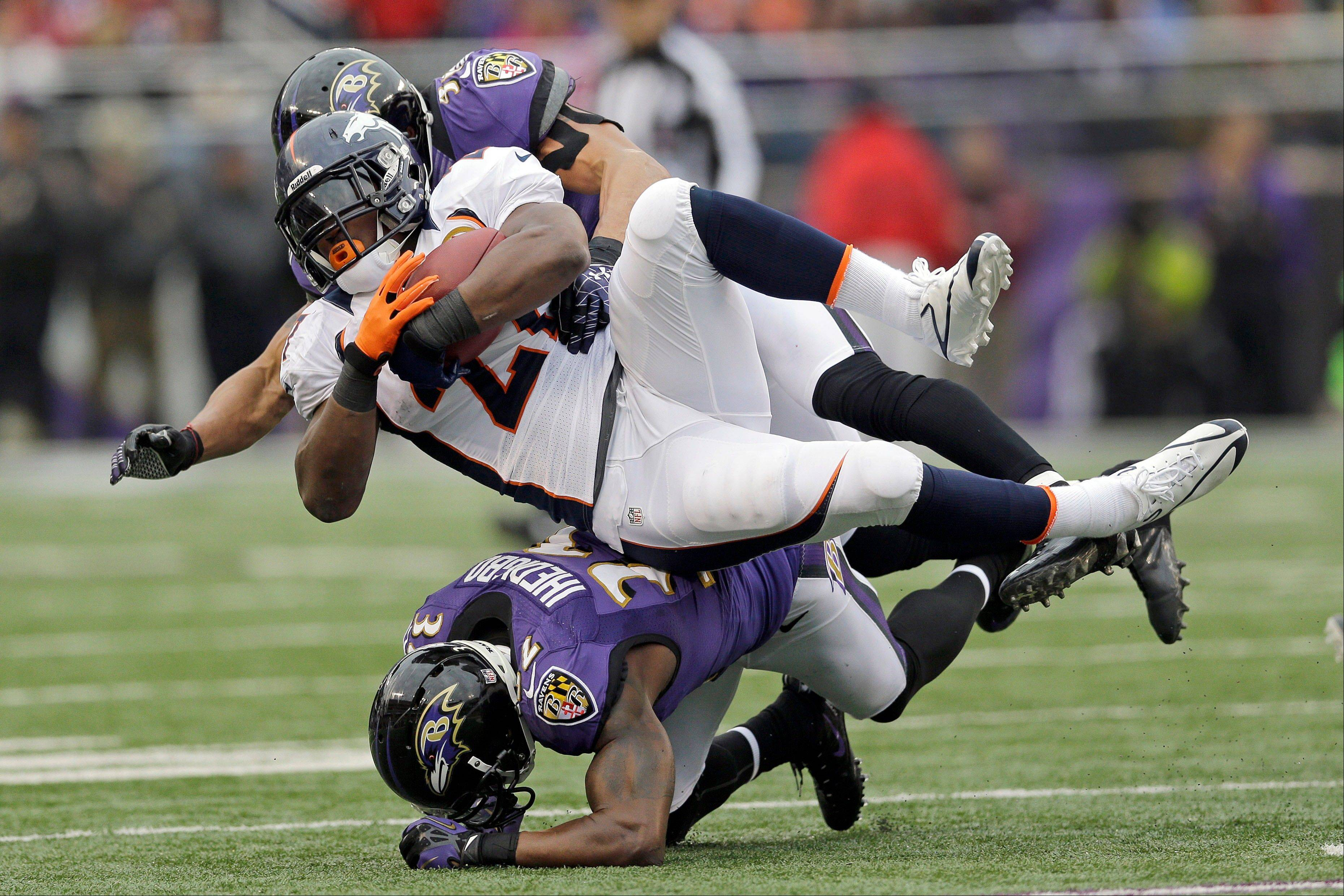 Denver Broncos running back Knowshon Moreno is stopped by Baltimore Ravens inside linebacker Brendon Ayanbadejo, top, and defensive back James Ihedigbo, bottom during the first half in Baltimore, Sunday.