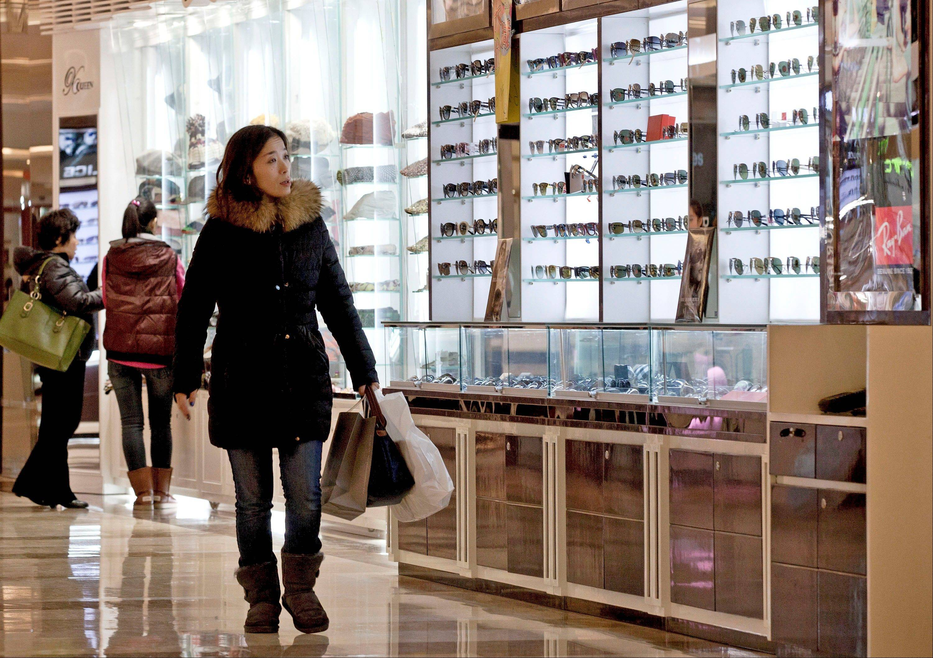 Chinese women look at the display at a shopping mall in Beijing Monday, Dec. 17, 2012. China�s new Communist Party leaders are promising reforms aimed at reducing reliance on exports to drive growth and more spending if needed to prop up a shaky economic recovery.