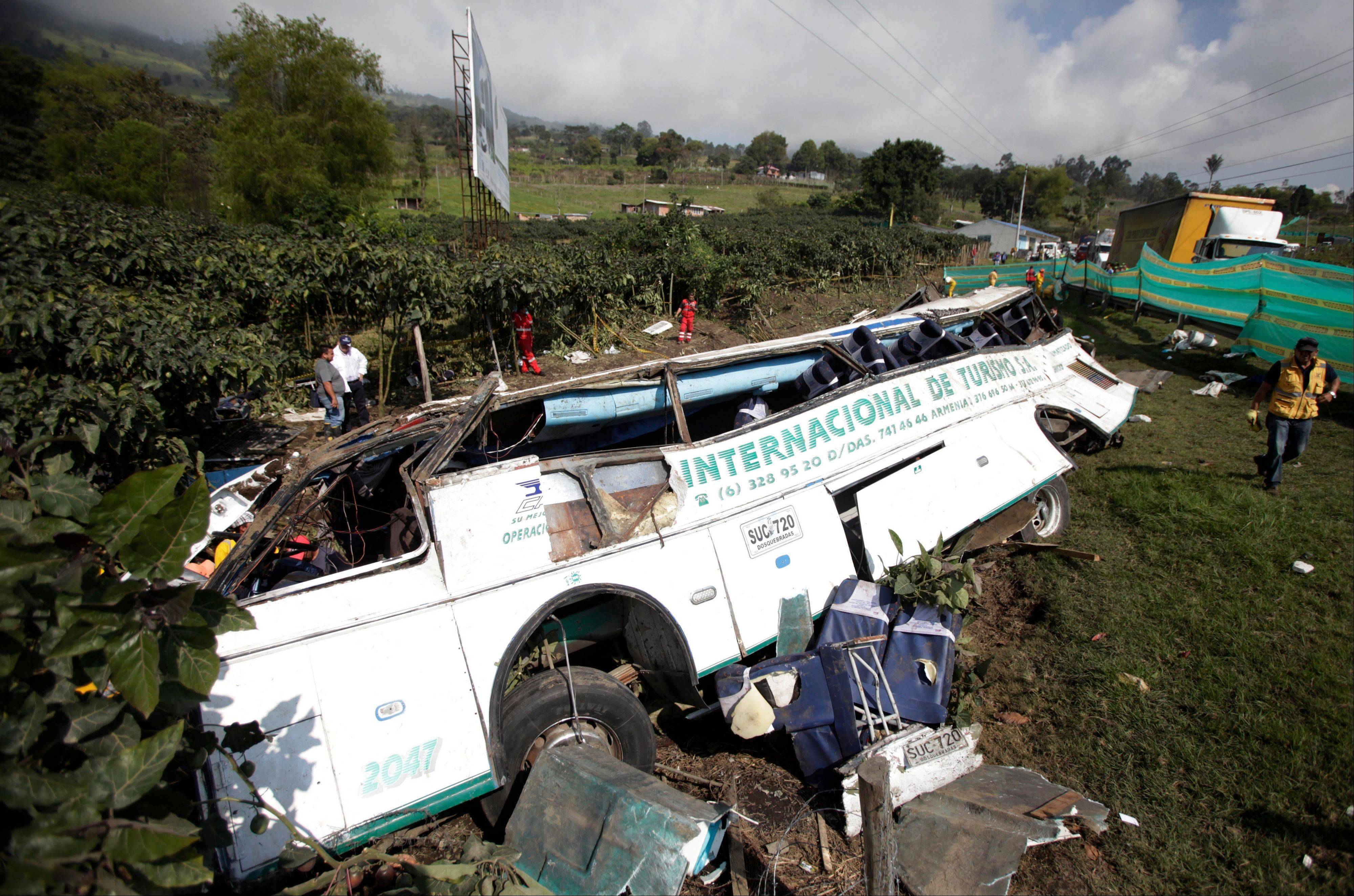 A charter bus that was in an single-vehicle accident lies on its side in San Raimundo, near Bogota, Colombia, Monday. The accident resulted in the death of at least 26 passengers and another 15 wounded.