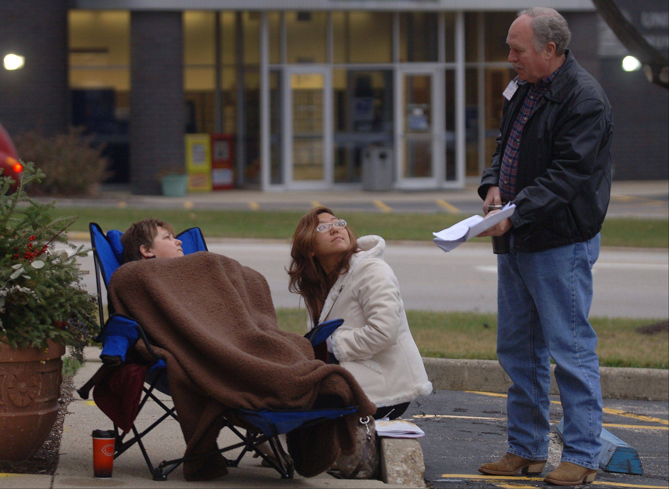 Mundelein trustee candidates Dawn Abernathy, left, and Holly Kim chat with mayor candidate Wally Frasier, right, outside the village hall early Monday morning as they wait for the doors to open to file their papers for the 2013 election. Abernathy arrived around 7 a.m. and kept warm under a blanket.