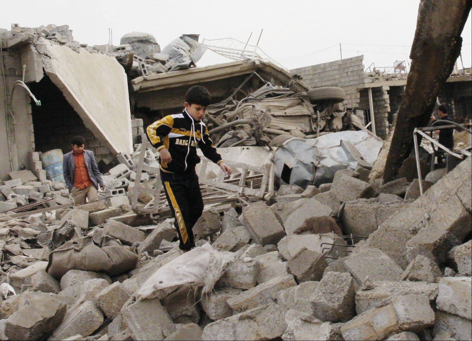 A boy walks in rubble at the scene of a car-bomb attack in al-Mouafaqiyah, a village inhabited by families from the Shabak ethnic group, near the city of Mosul, 225 miles northwest of Baghdad, Iraq, Monday.