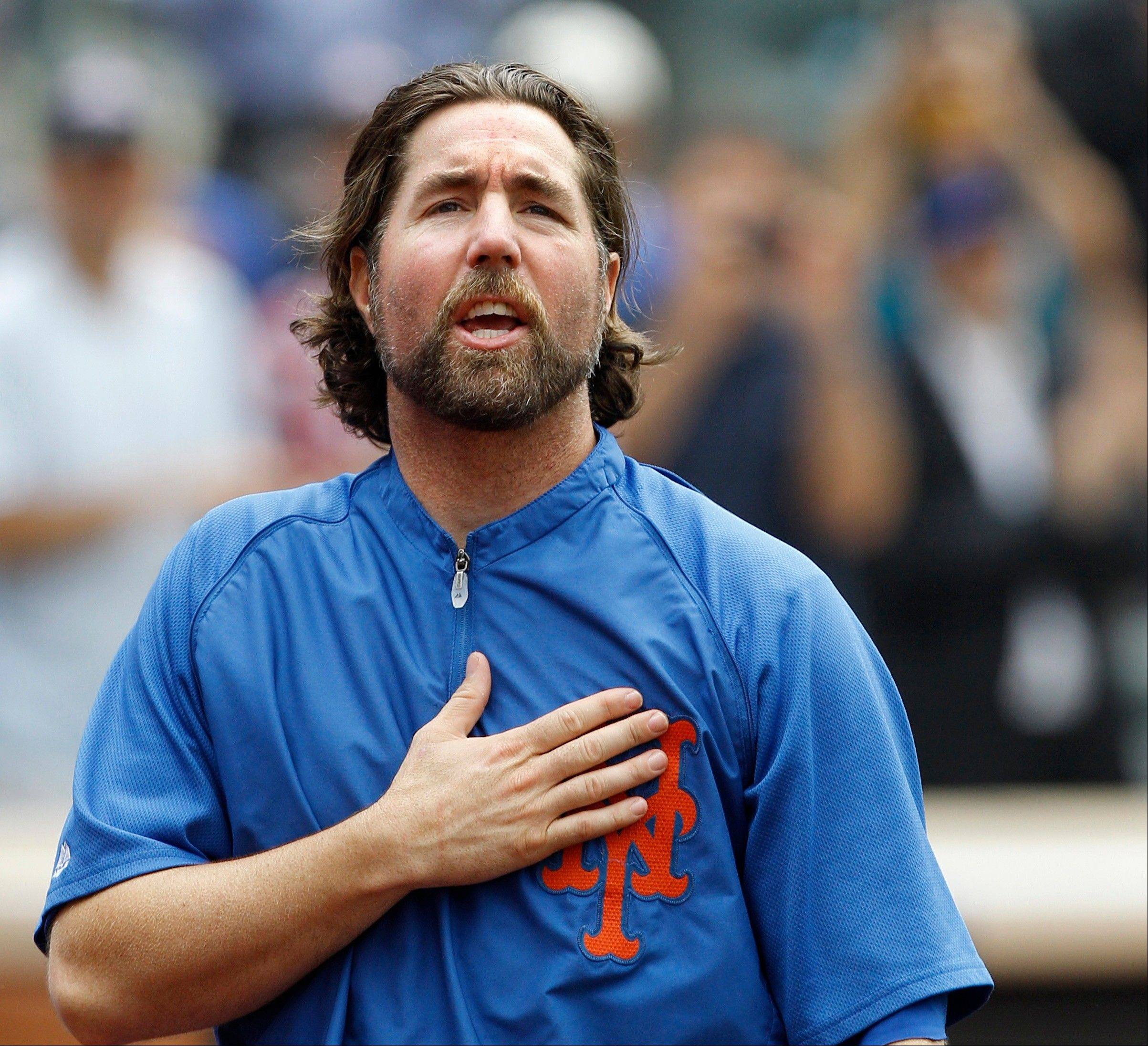 This Sept. 27, 2012 file photo shows New York Mets starting pitcher R.A. Dickey reacting to fans as he celebrates his 20th victory of the season after the Mets 6-5 win against the Pittsburgh Pirates in a baseball game at Citi Field in New York. A person familiar with the deal tells The Associated Press that Dickey and the Blue Jays have agreed on a new contract, clearing the way for the New York Mets to trade the Cy Young winner to Toronto. The 38-year-old knuckleballer must pass a physical before he joins the Blue Jays. The Mets would get prized catching prospect Travis d'Arnaud as the centerpiece of the multiplayer swap.