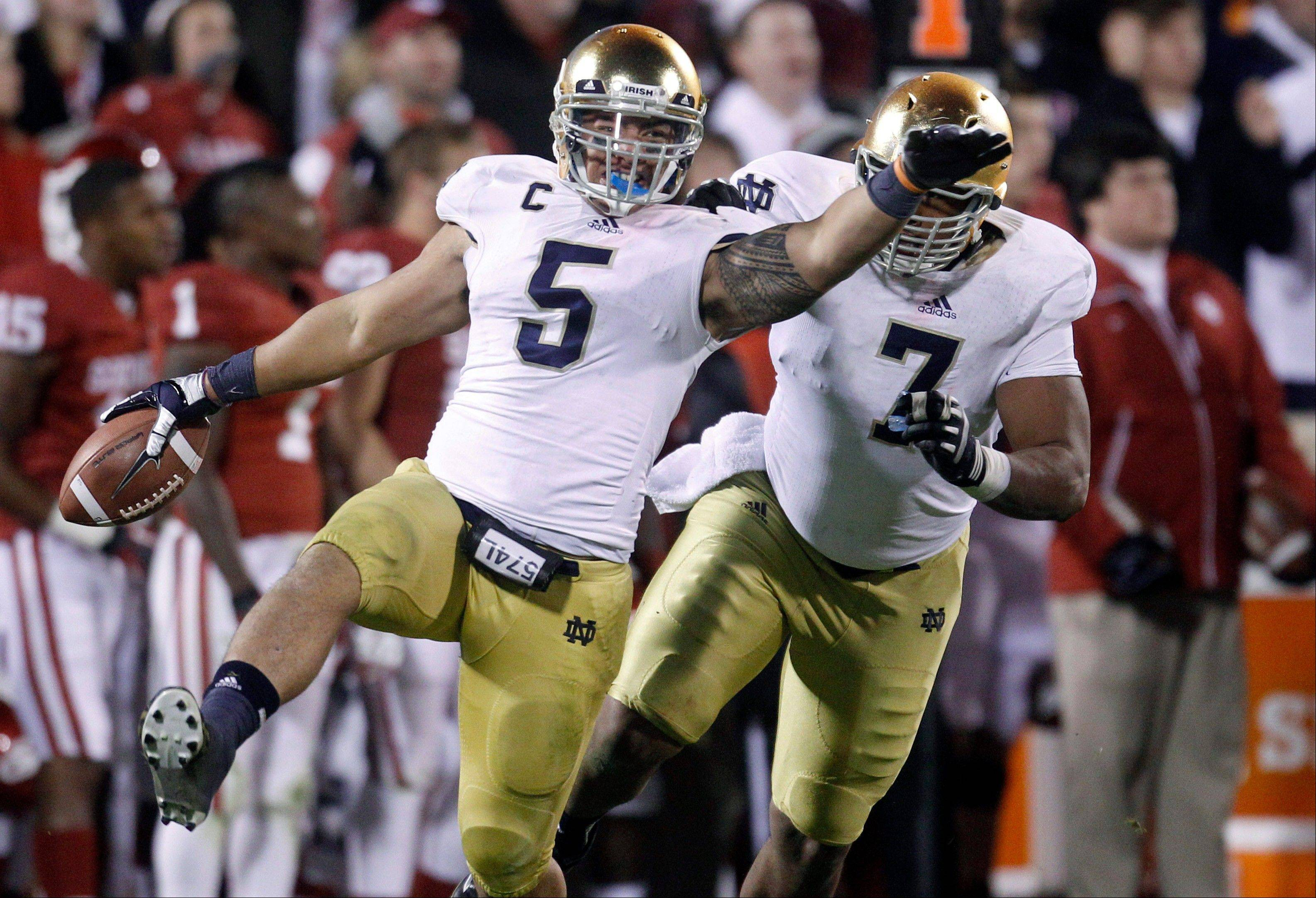 In this Oct. 27, 2012 file photo, Notre Dame linebacker Manti Te�o (5) celebrates with teammate Stephon Tuitt (7) after an interception against Oklahoma in the fourth quarter of an NCAA college football game in Norman, Okla. Te�o and the Irish will play Alabama for the national championship, the highlight of this year�s 35 bowl games.
