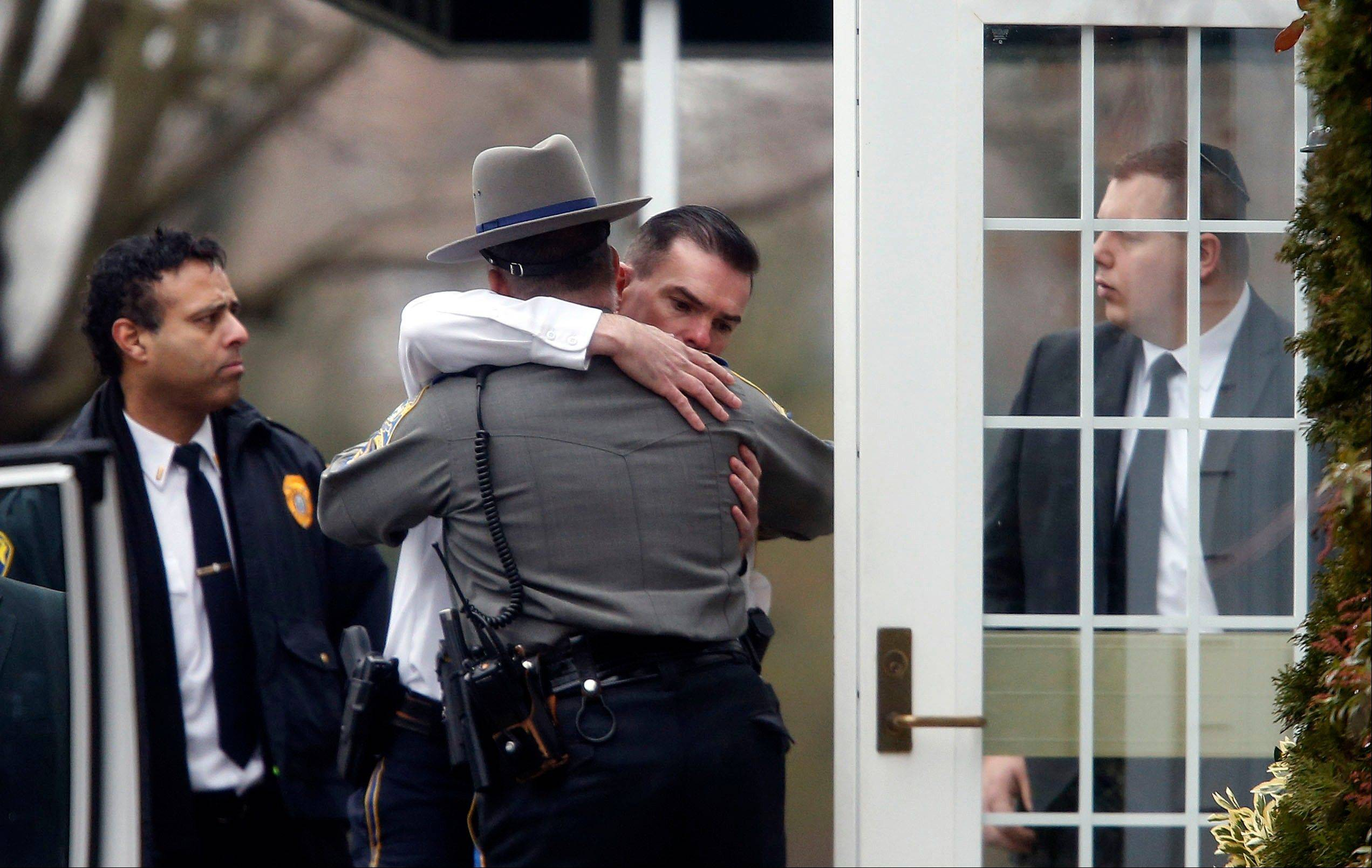 Police officers comfort one another outside a funeral service for 6-year-old Noah Pozner, Monday, Dec. 17, 2012, in Fairfield, Conn. Pozner was killed when a gunman walked into Sandy Hook Elementary School in Newtown Friday and opened fire, killing 26 people, including 20 children.