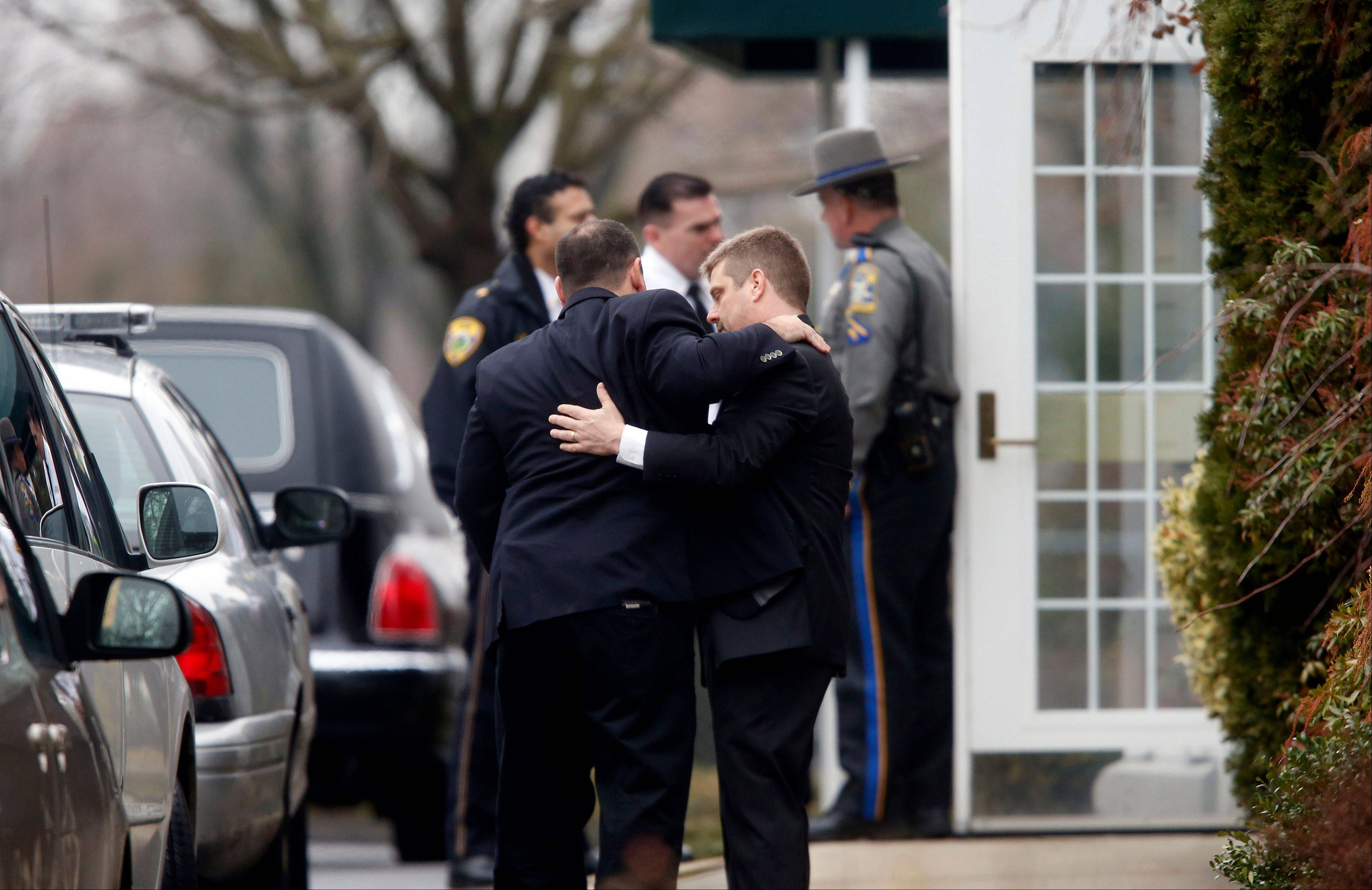 A mourner is comforted as he arrives at a funeral service for 6-year-old Noah Pozner, Monday, Dec. 17, 2012, in Fairfield, Conn. Pozner was killed when a gunman walked into Sandy Hook Elementary School in Newtown Friday and opened fire, killing 26 people, including 20 children.
