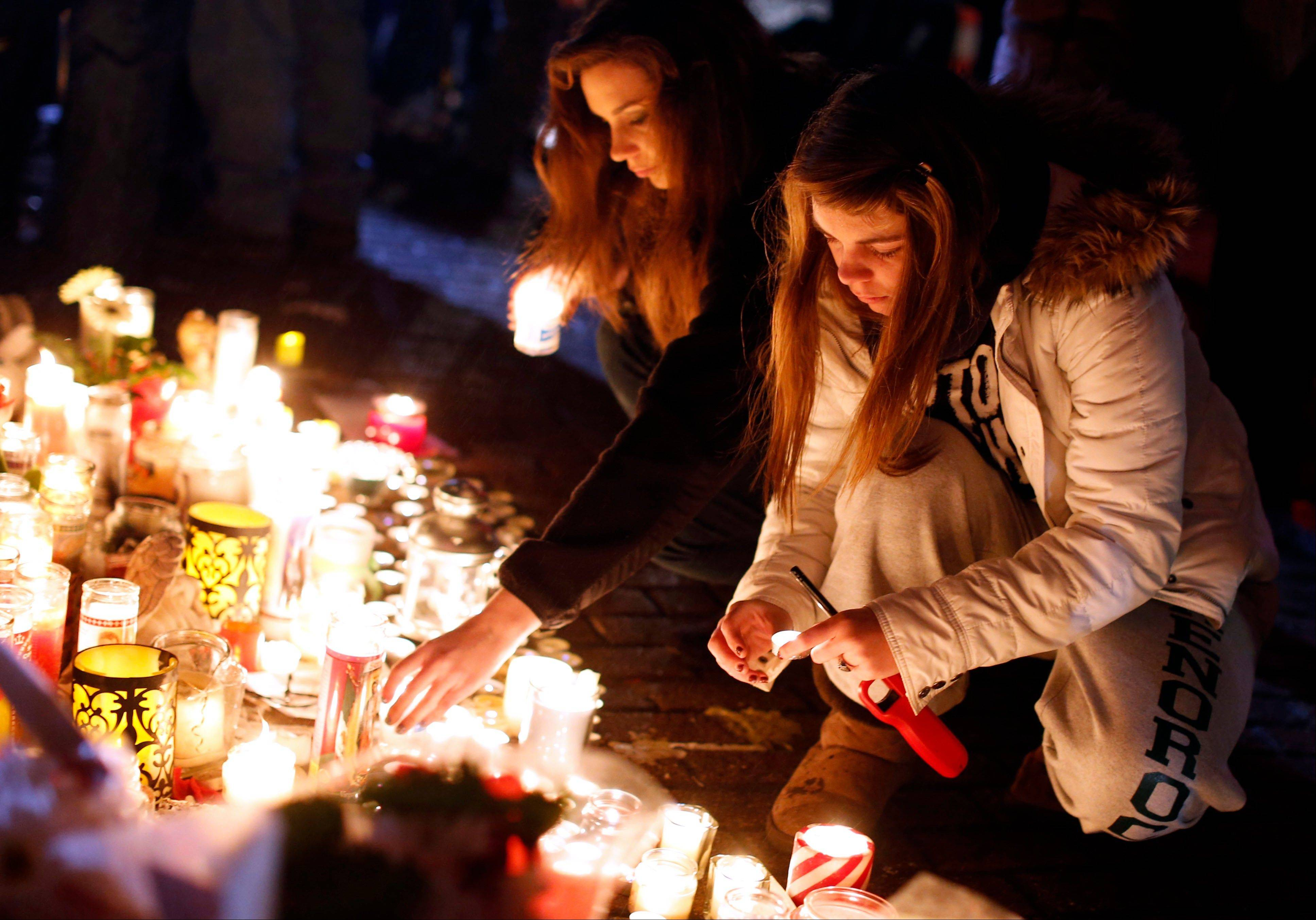 Visitors light candles at a memorial to shooting victims, Monday, Dec. 17, 2012, in Newtown, Conn. A gunman walked into Sandy Hook Elementary School in Newtown Friday and opened fire, killing 26 people, including 20 children.