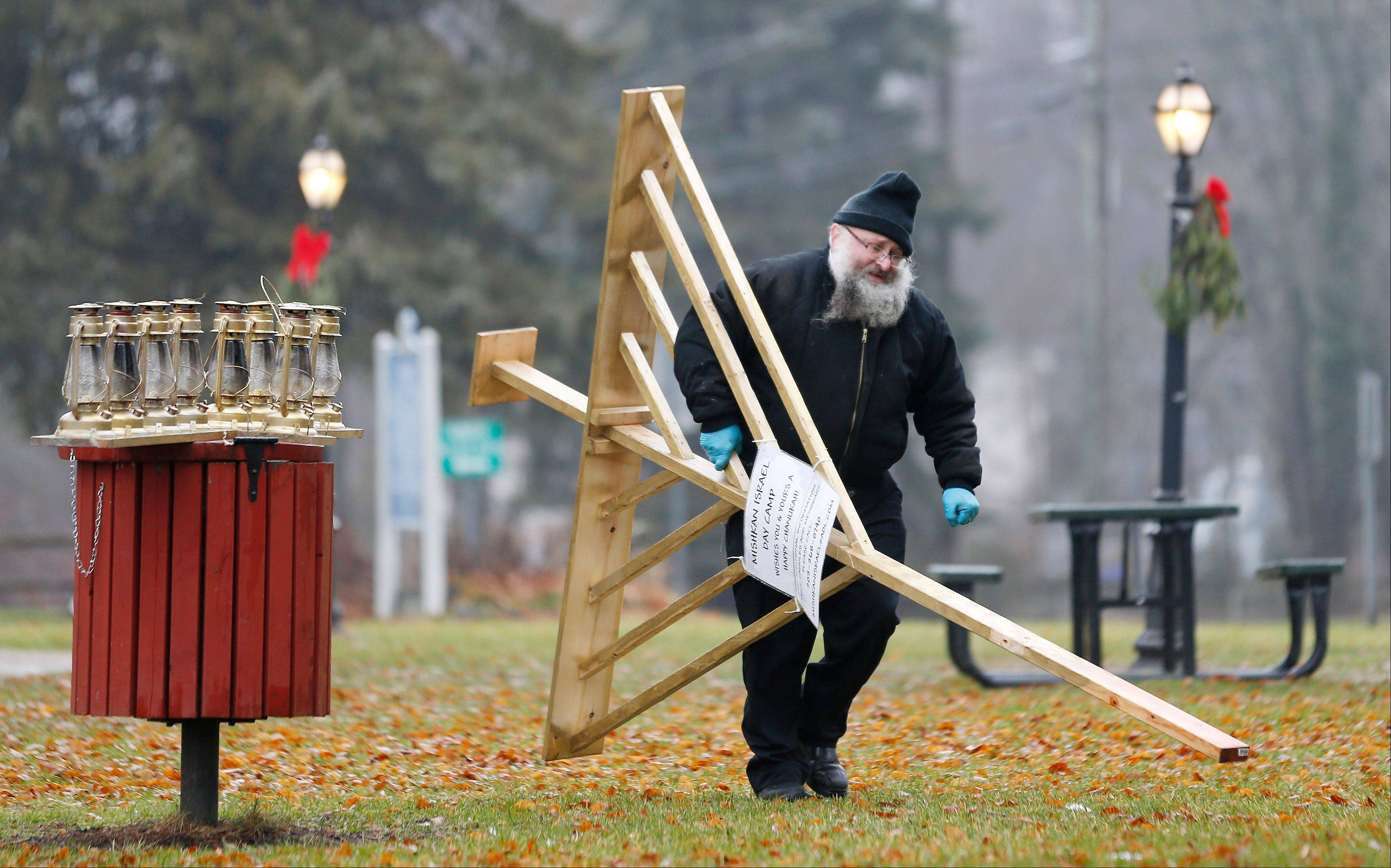 Rabbi Joseph Stock breaks down a Menorah at the completion of Hanukkah in the town square area of Monroe, Conn., where shooting victim Noah Pozner will be buried later in the day, Monday, Dec. 17, 2012. Stock will attend the burial services for the 6-year-old at B'nai Israel Cemetery. On Friday, a gunman allegedly killed his mother at their home and then opened fire inside the Sandy Hook Elementary School in Newtown, killing 26 people, including 20 children.