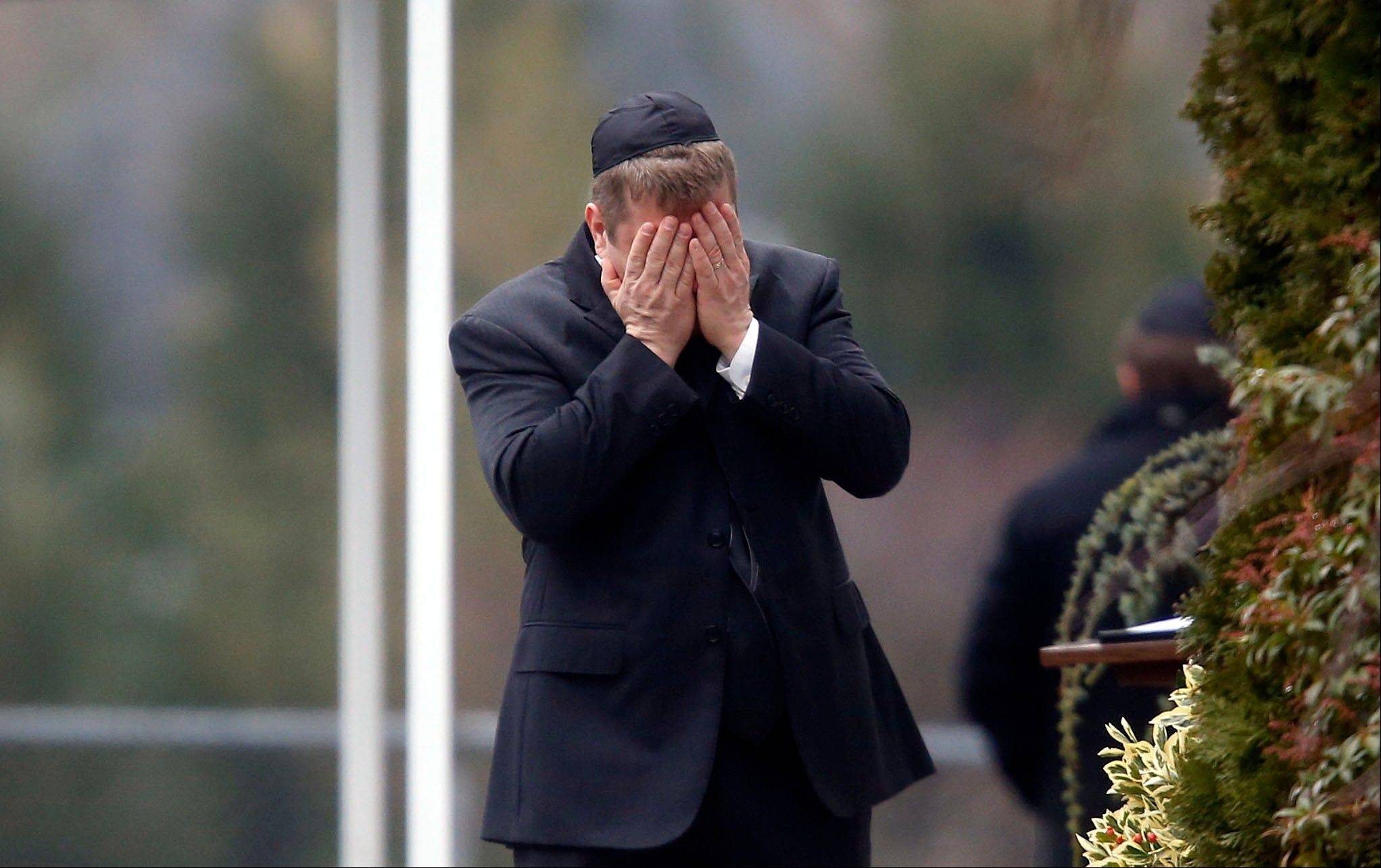 A mourner arrives at the funeral service for 6-year-old Noah Pozner, Monday, Dec. 17, 2012, in Fairfield, Conn. Pozner was killed when a gunman walked into Sandy Hook Elementary School in Newtown Friday and opened fire, killing 26 people, including 20 children.
