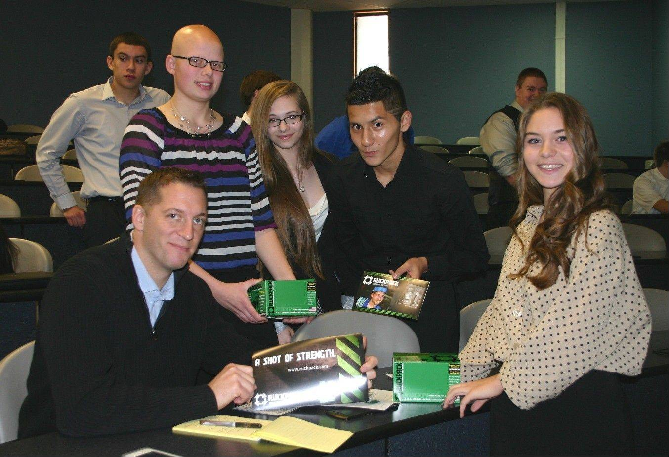 Rob Dyer, left, a Marine Corps veteran, entrepreneur and creator of the nutritional drink RuckPack, meets with Lake Park High School marketing students Sam Cummings, Sara Bobek, Mauricio Cardona and Cassidy McGinn. The students pitched marketing ideas for RuckPack to Dyer for their semester-end project.