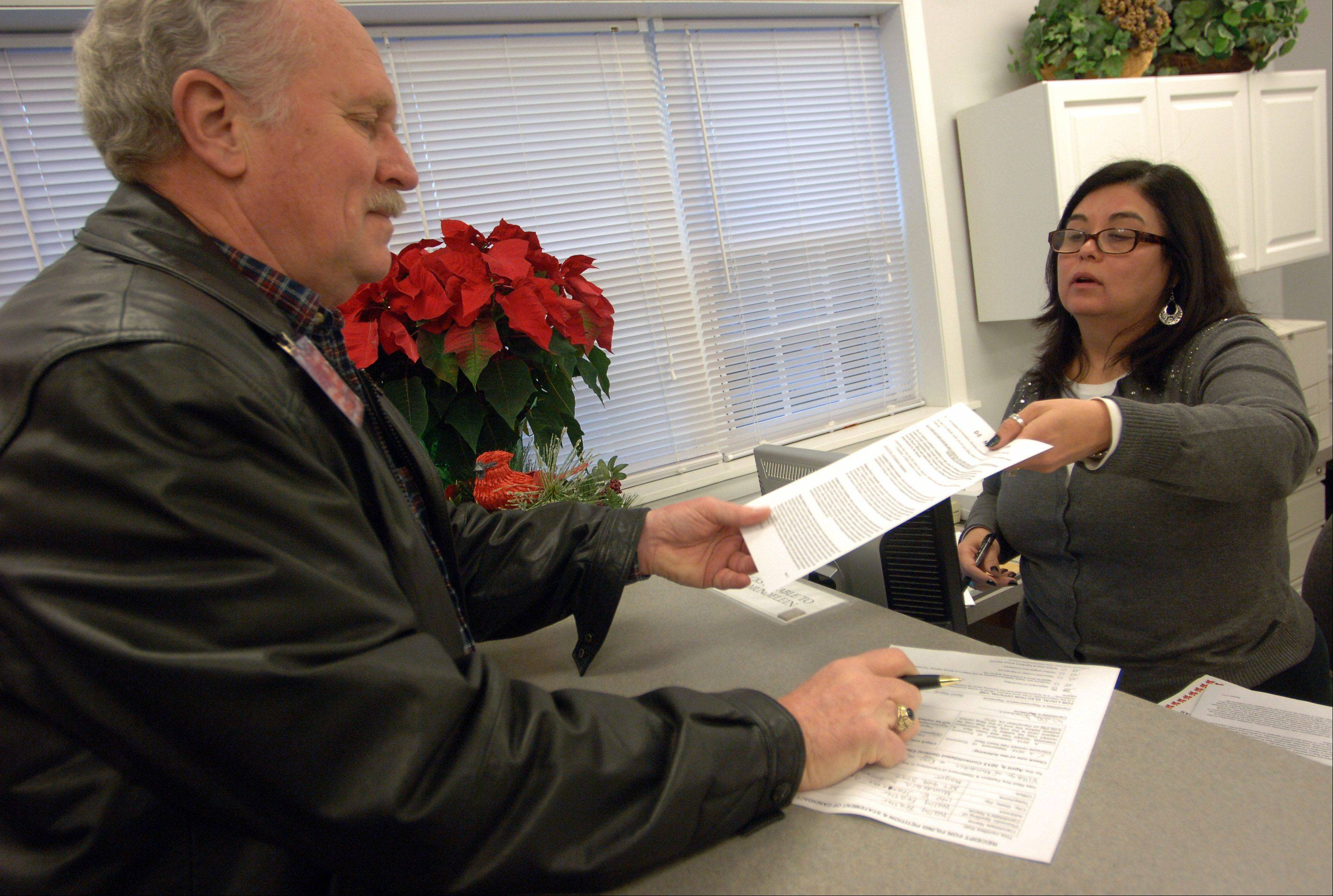 Mundelein mayoral candidate Wally Frasier files his papers with village clerk Esmie Dahlstrom Monday morning at the village hall.
