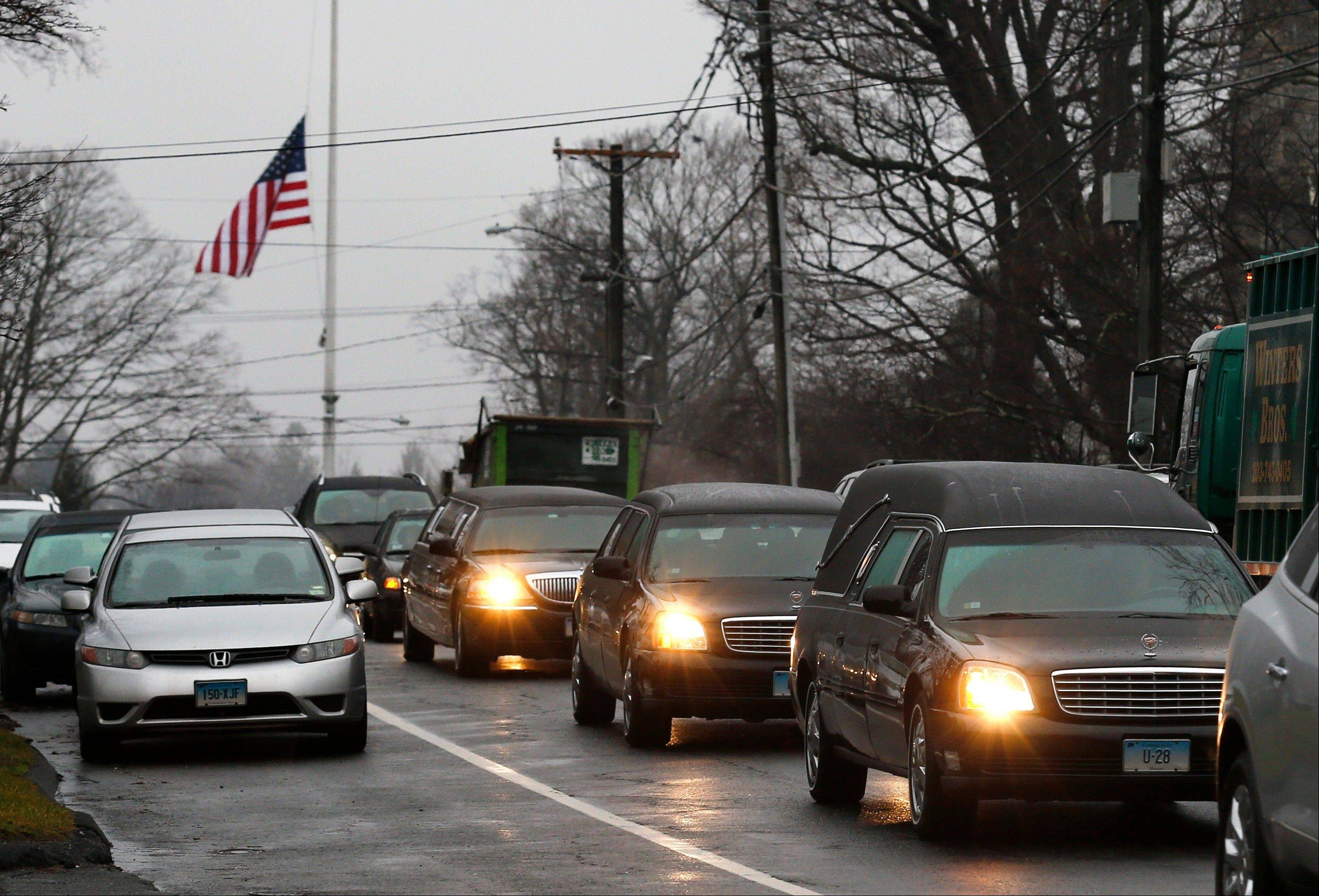 A hearse and family limousines for 6-year-old shooting victim Jack Pinto rolls past a flag at half-staff Monday as the funeral procession heads through the historic district in Newtown, Conn. A gunman opened fire on Friday at Sandy Hook Elementary School in the town, killing 26 people, including 20 children before killing himself.