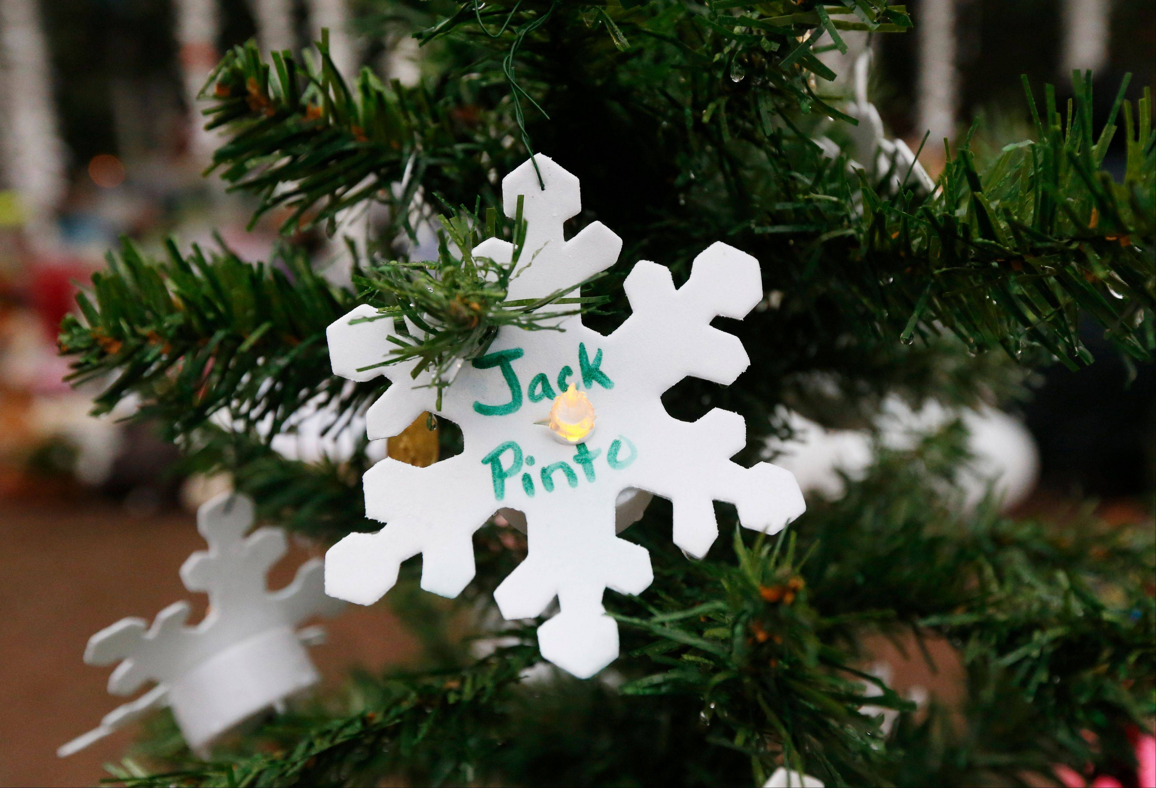 A snowflake ornament with the name of 6-year-old Jack Pinto hangs on a Christmas tree at a makeshift memorial in the Sandy Hook village of Newtown, Conn., Monday, Dec. 17, 2012, as the town mourns victims killed in Friday's school shooting. Pinto, who was killed Friday when gunman Adam Lanza opened fire inside the Sandy Hook Elementary School, will be buried Monday.