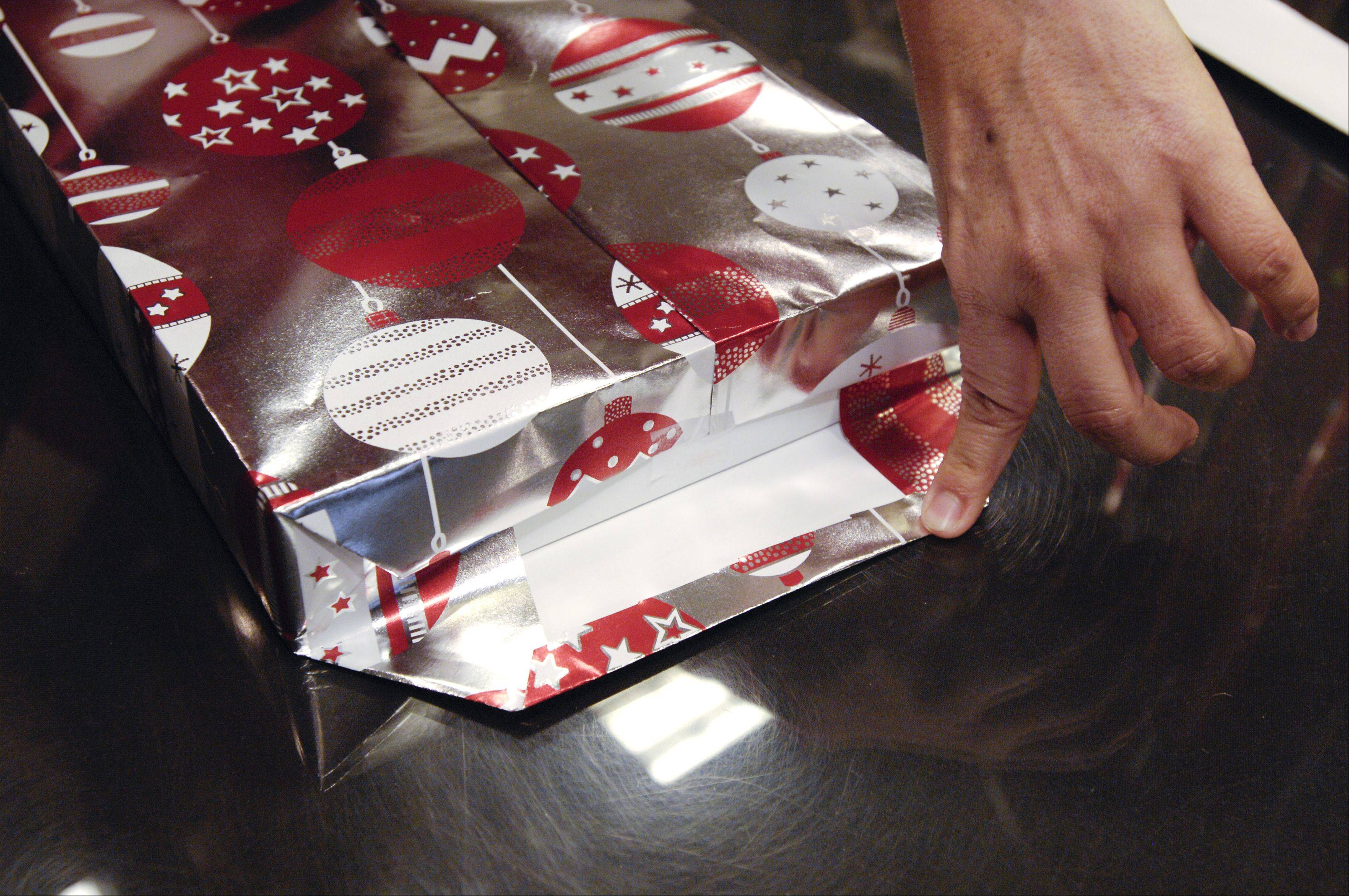 Step 7: Fold the ends into triangles and fold the top edge. Tape to the side of the box.