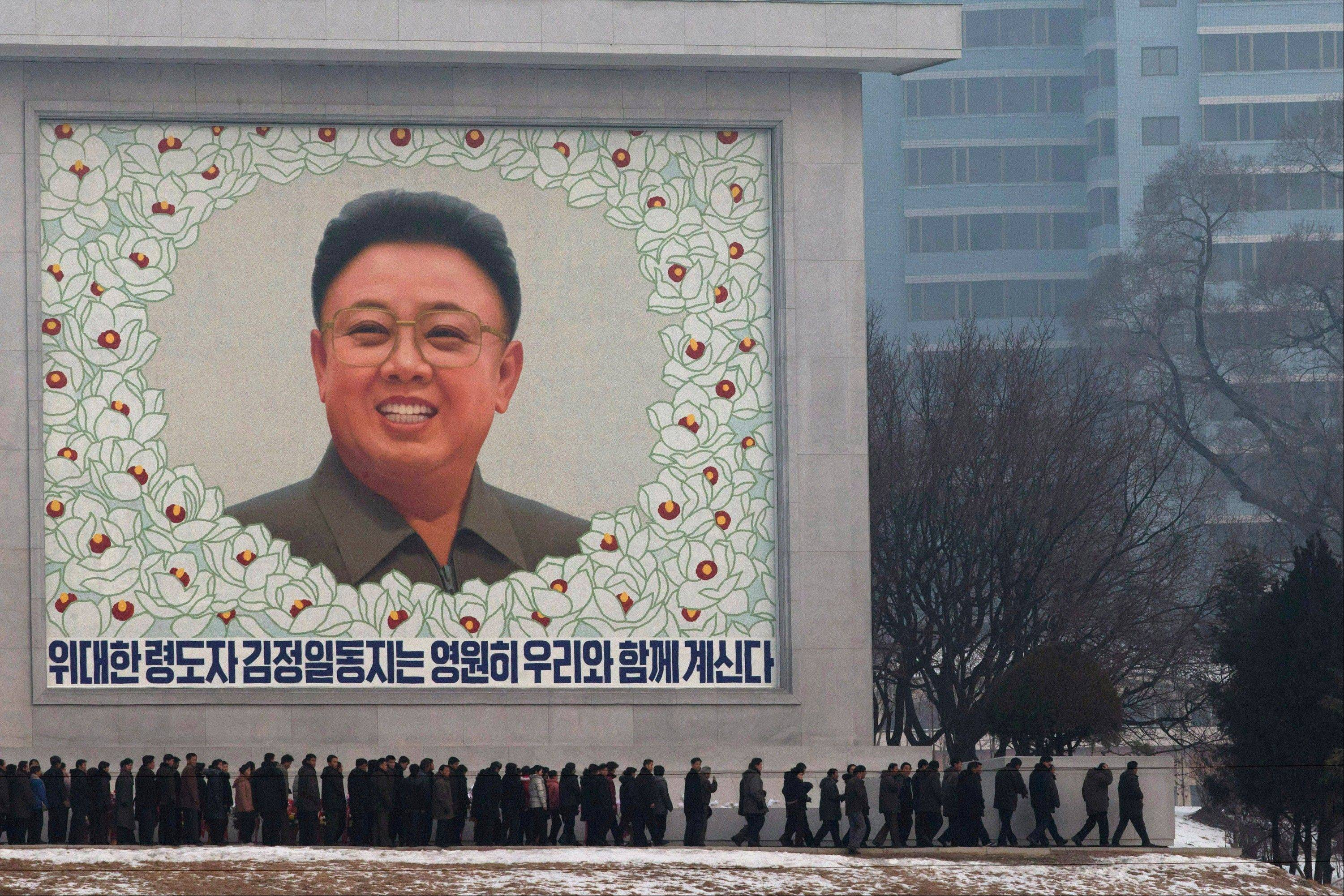 North Koreans pay respect in front of a mosaic of the late North Korean leader Kim Jong Il on the eve of his first death anniversary in Pyongyang, North Korea, Sunday.