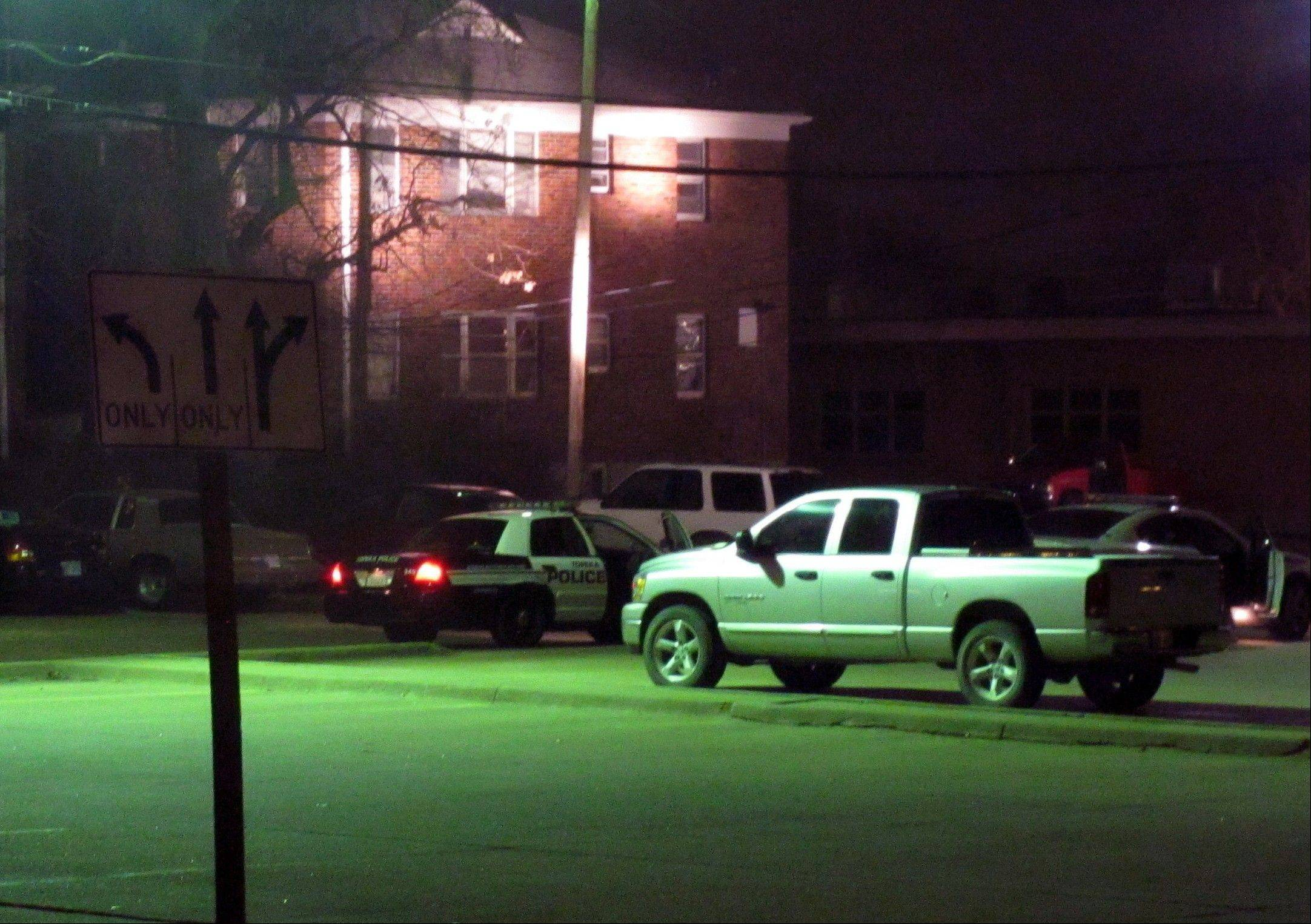 Law enforcement vehicles surround the backside of an apartment complex evacuated by authorities as they hunted for a 22-year-old man suspected of fatally shooting two police officers Sunday in Topeka, Kan.