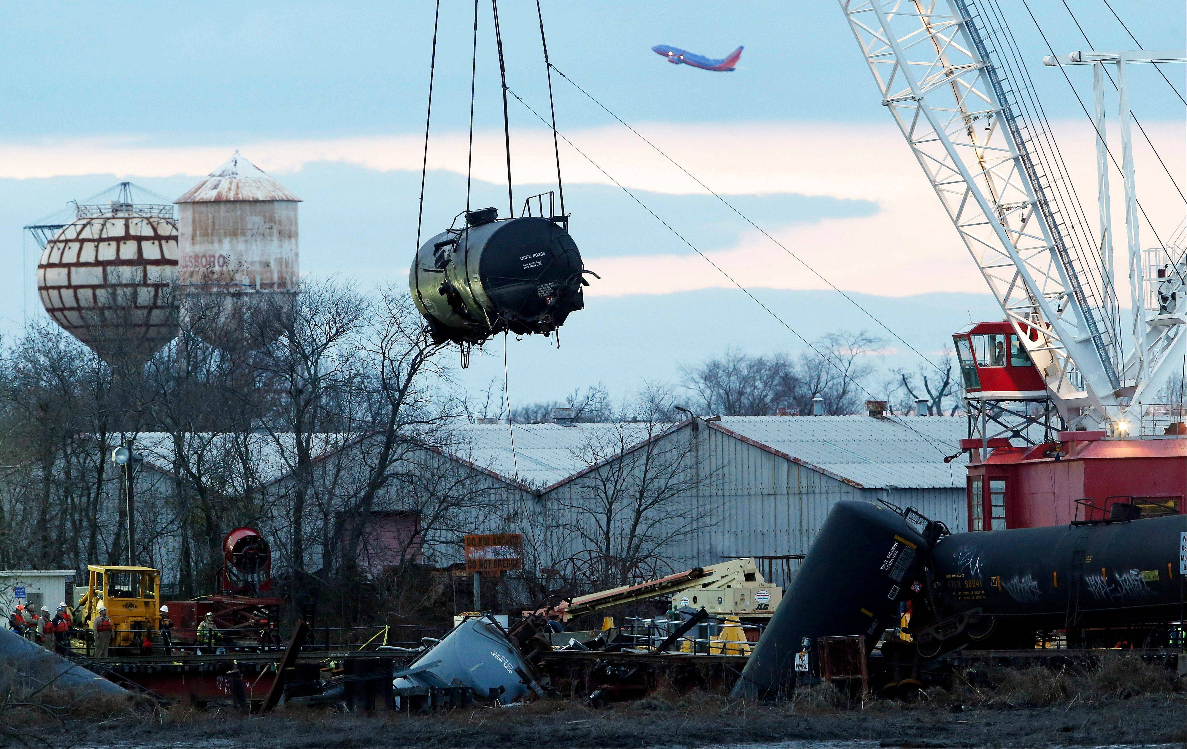 A train tank car dangles from a crane as it is pulled up from the crash site on a small bridge on the Mantua Creek last Tuesday in Paulsboro, N.J.