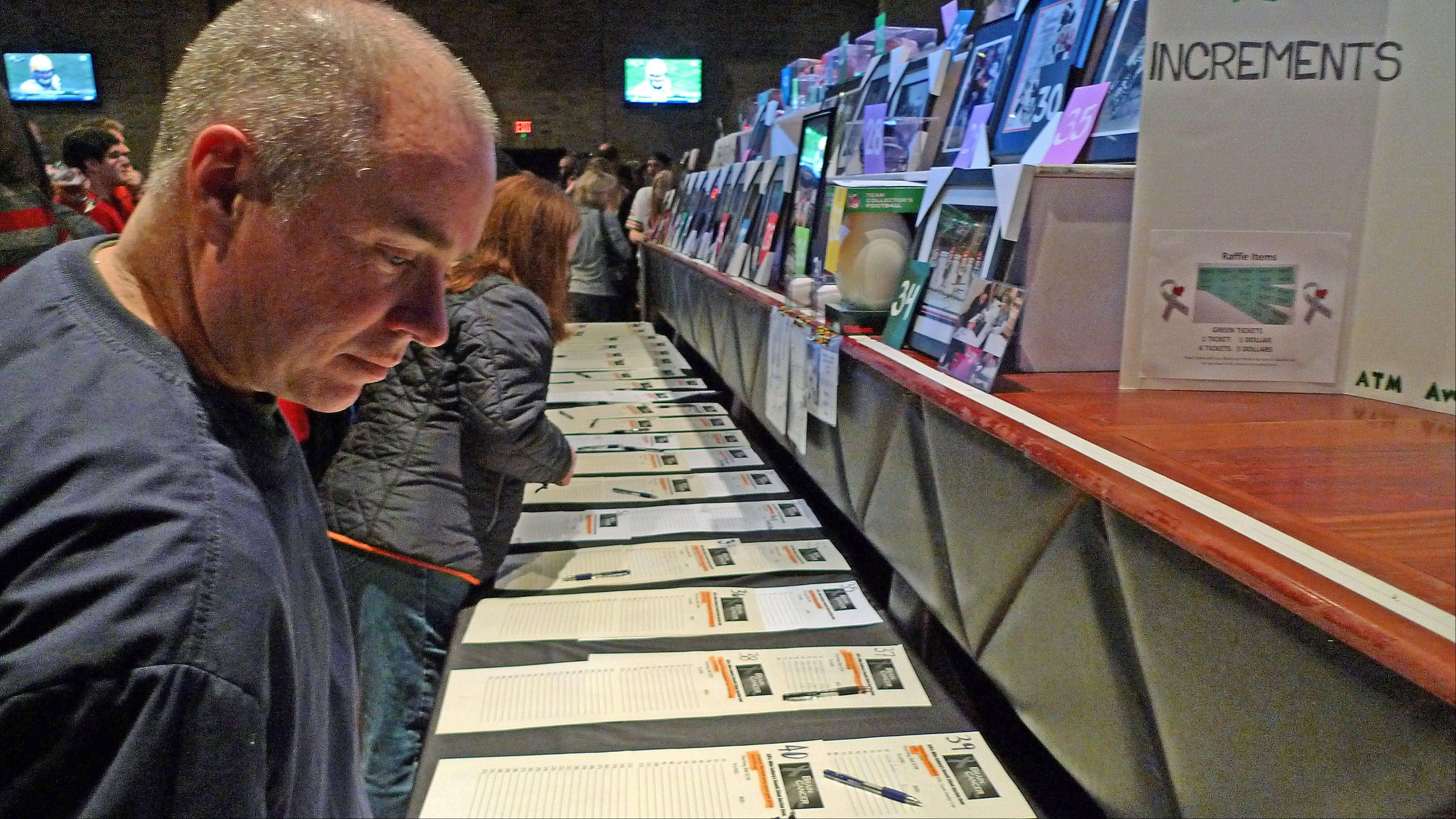 Elk Grove Village resident Tim O'Malley, a Skokie firefighter, looks over silent auction items Sunday at a fundraiser for Schaumburg firefighter Mike Solberg, who is recovering from brain cancer surgery.