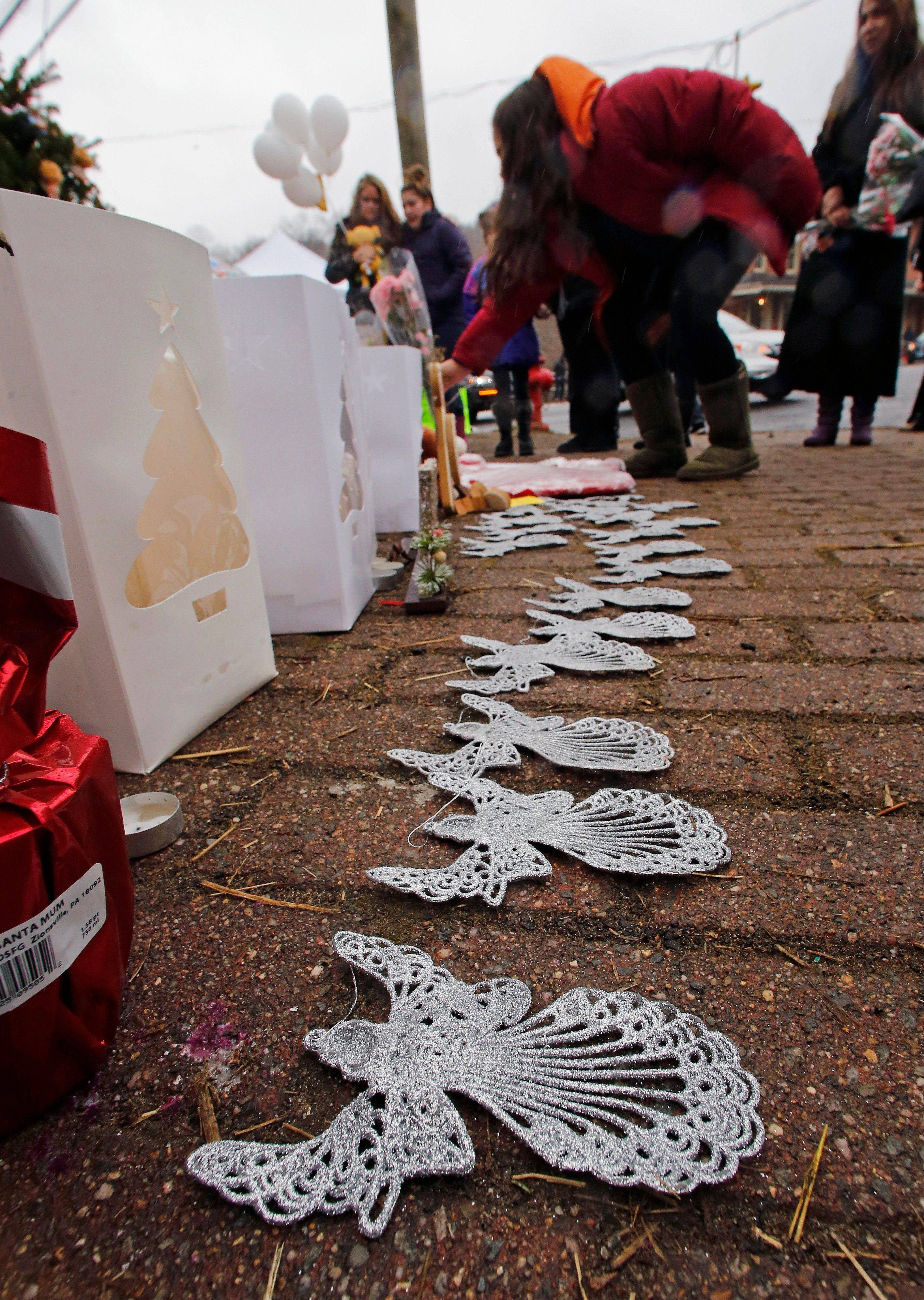 A woman lays flowers at the site of a makeshift memorial for school shooting victims Sunday in the village of Sandy Hook in Newtown, Conn. A gunman opened fire at Sandy Hook Elementary School in the town, killing 26 people, including 20 children before killing himself on Friday.