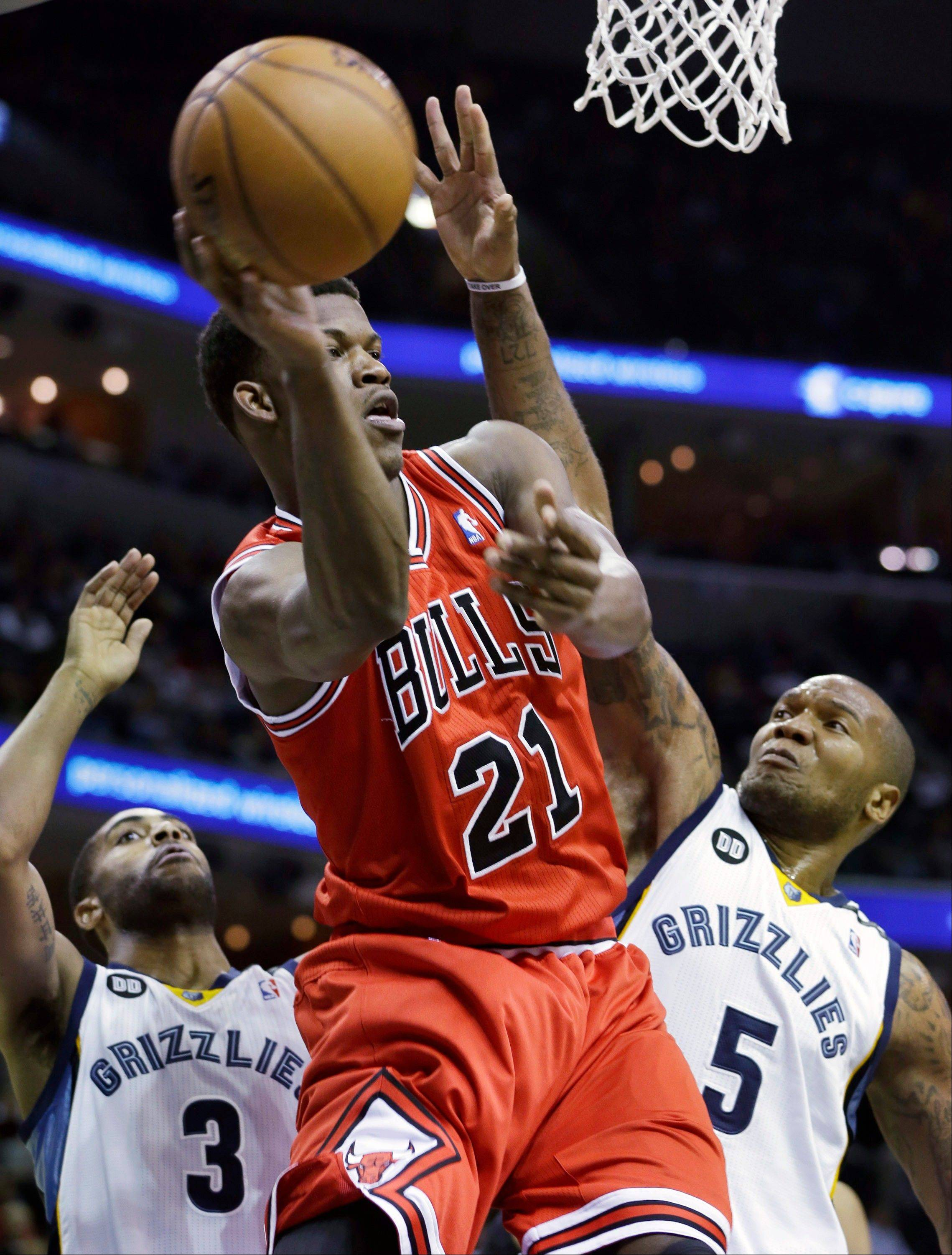 Chicago Bulls' Jimmy Butler (21) gets an offensive rebound next to Memphis Grizzlies' Wayne Ellington (3) and Marreese Speights (5) during first half of an NBA basketball game Monday night in Memphis, Tenn. The Bulls would go on to lose 80-71.