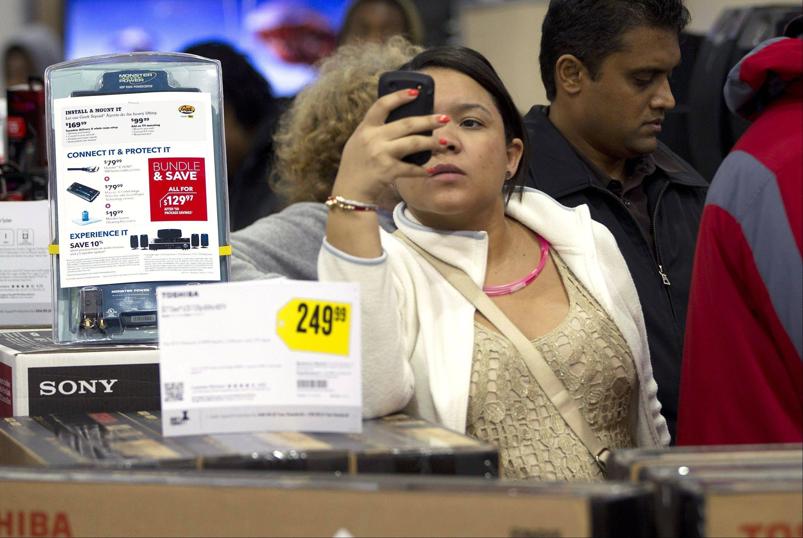 A shopper uses her smartphone at a Best Buy in Pembroke Pines, Fla. Shoppers� actions on Facebook and elsewhere online help dictate what�s in stores during this holiday season.
