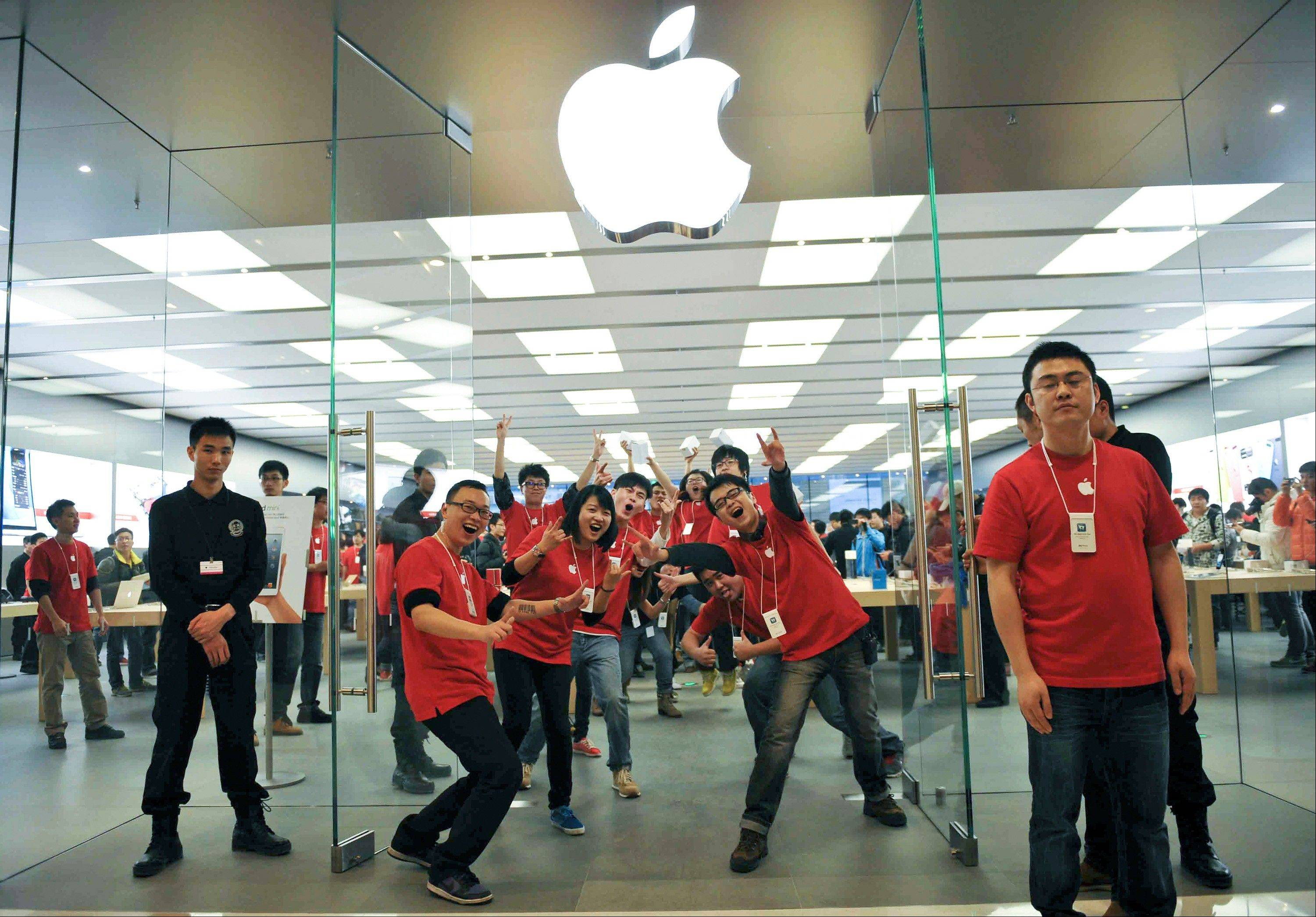 Chinese employees pose for photographers at the newly opened Apple Store at the MixC mall in Chengdu in southwest China's Sichuan province on Saturday, Dec. 15, 2012. Apple Computer currently has eight stores in mainland China. (AP Photo) CHINA OUT