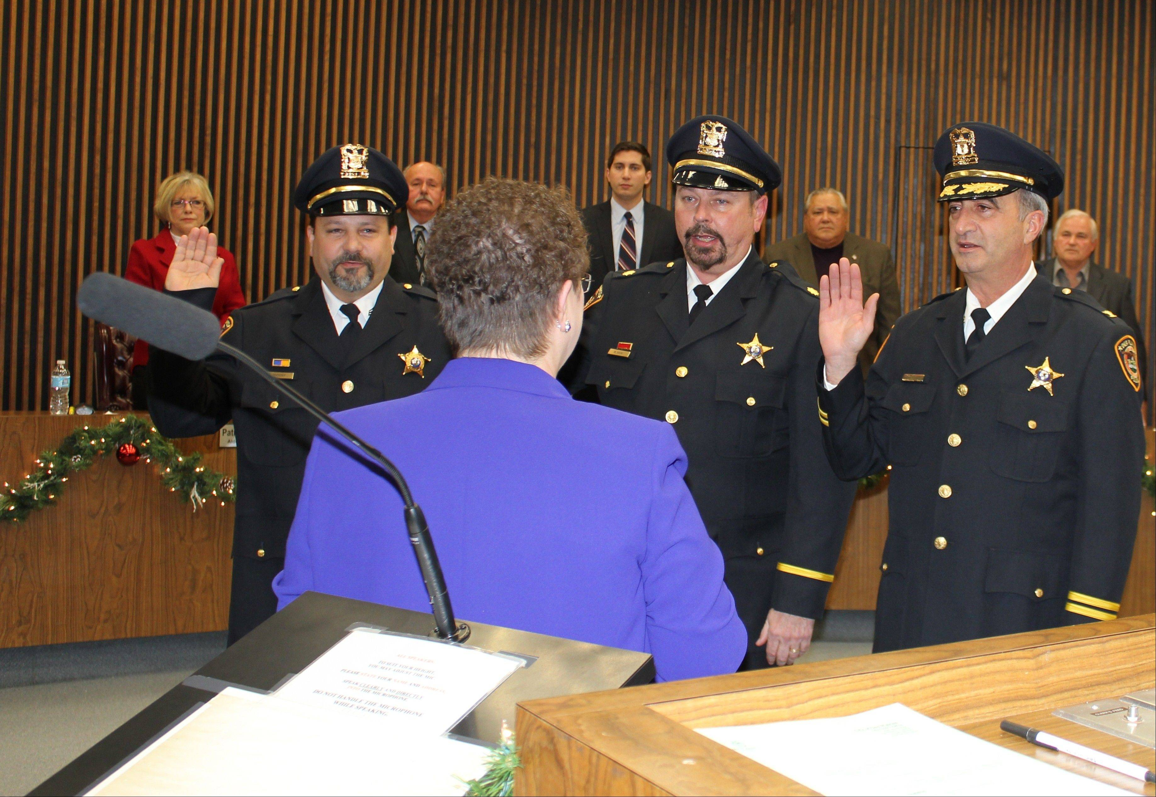 From left, Detective Jeffrey Jacoby, Sgt. Randy Akin, and Cmdr. Nicholas Treantafeles are sworn into their new positions of sergeant, commander, and deputy chief, respectively, with the Des Plaines Police Department by City Clerk Gloria Ludwig during Monday night's City Council meeting.
