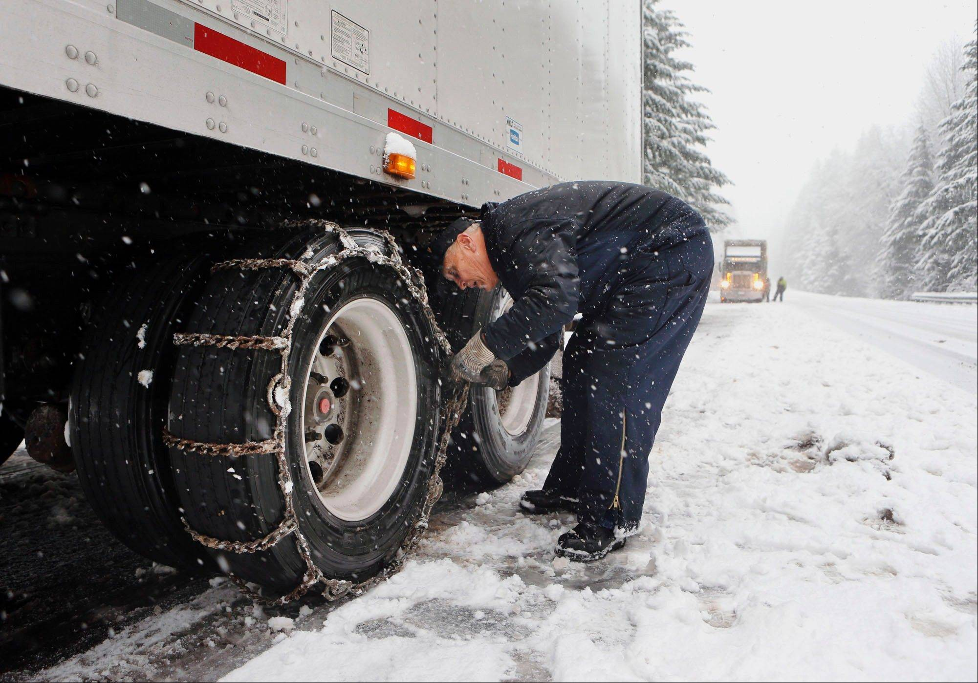 Del Queener of Puyallup, Wash., puts chains on his truck trailer tires as he prepares to drive over Willamette Pass, Ore., during a snow storm Monday.