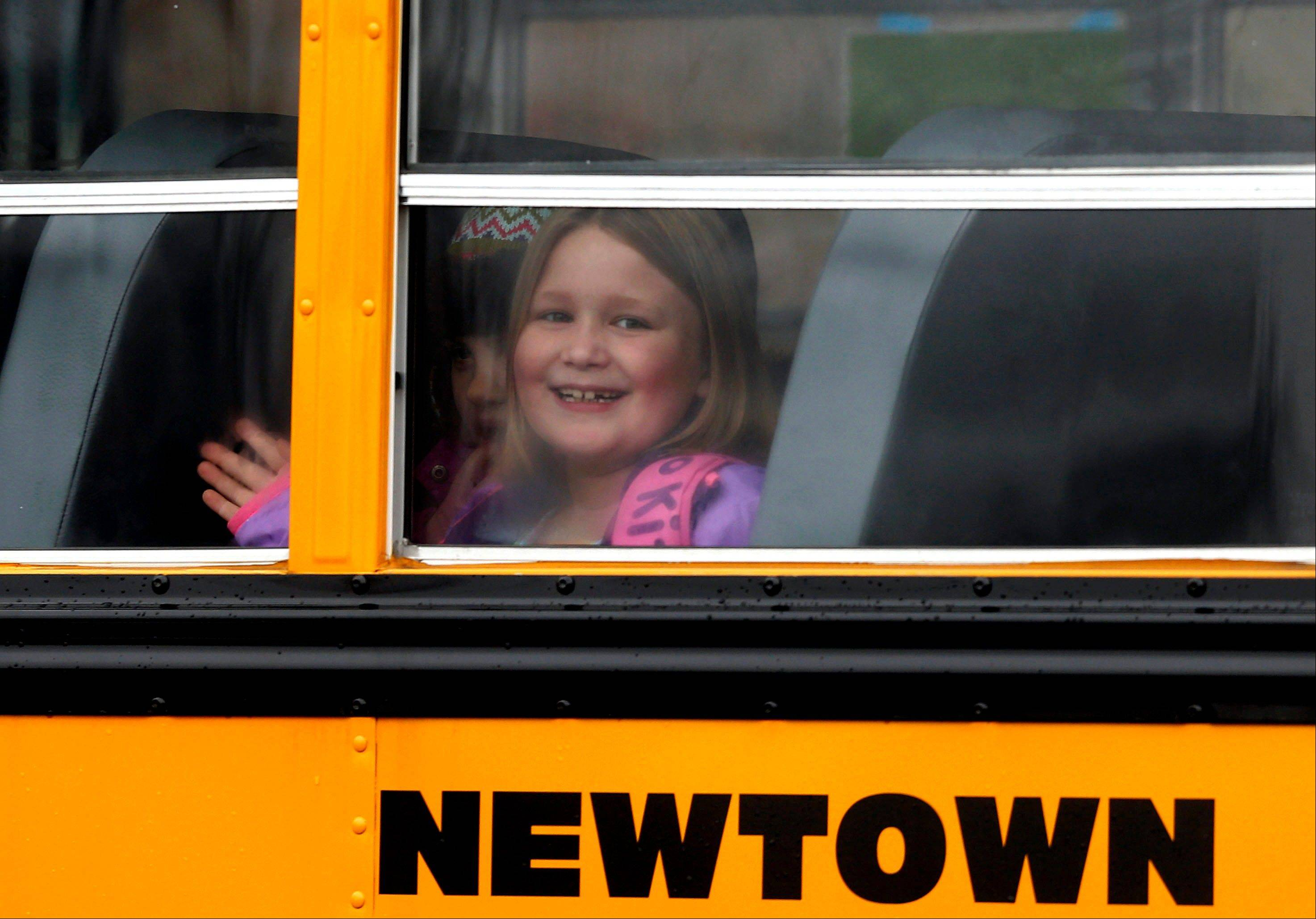 A young girl waves as her school bus pulls into Hawley School, Tuesday, Dec. 18, 2012, in Newtown, Conn. Classes resume Tuesday for Newtown schools except those at Sandy Hook. Buses ferrying students to schools were festooned with large green and white ribbons on the front grills, the colors of Sandy Hook.