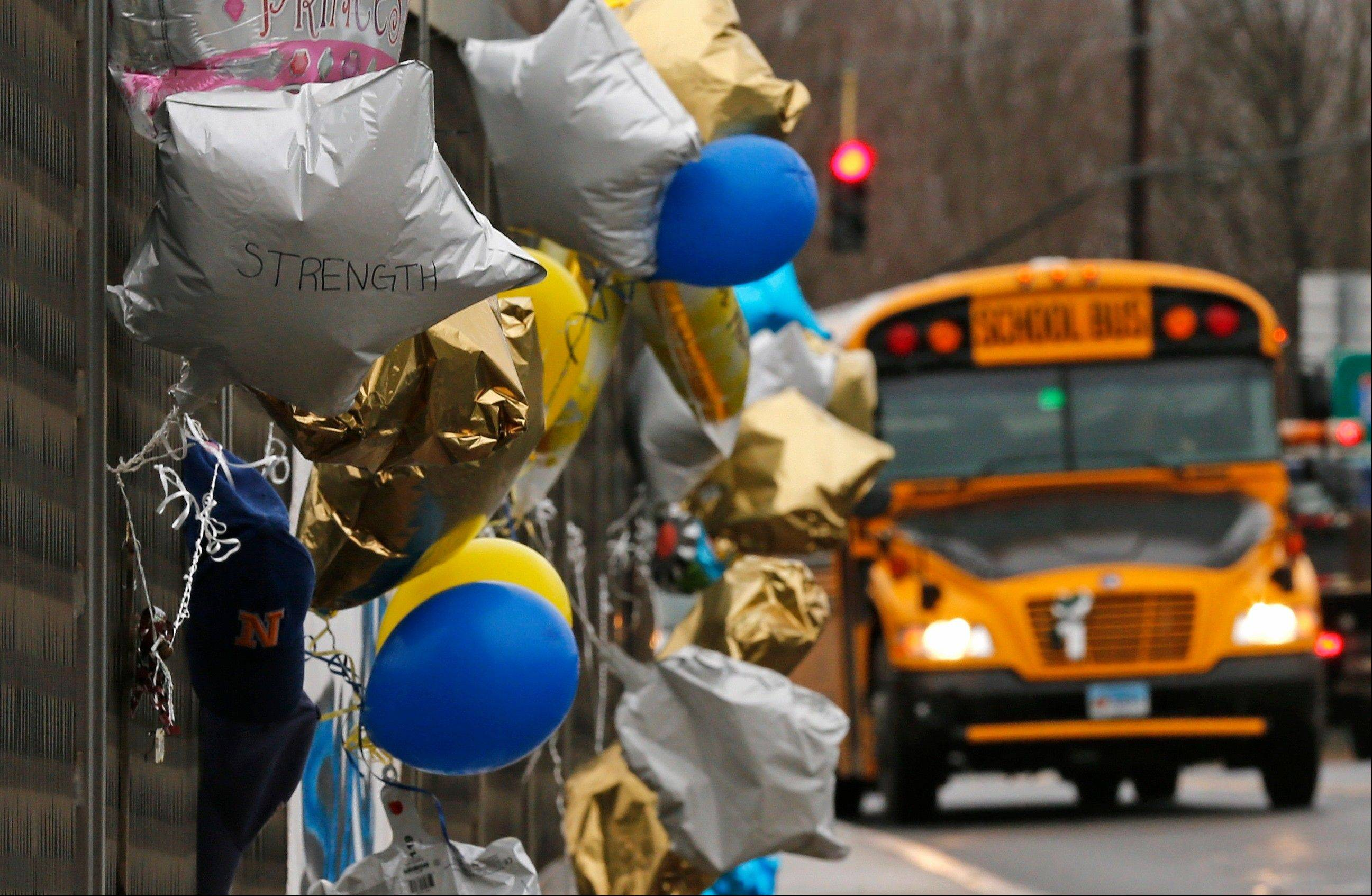 A school bus rolls toward a memorial for victims of the school shooting in Newtown, Conn., Tuesday, Dec. 18, 2012. Classes resume Tuesday for Newtown schools except those at Sandy Hook.