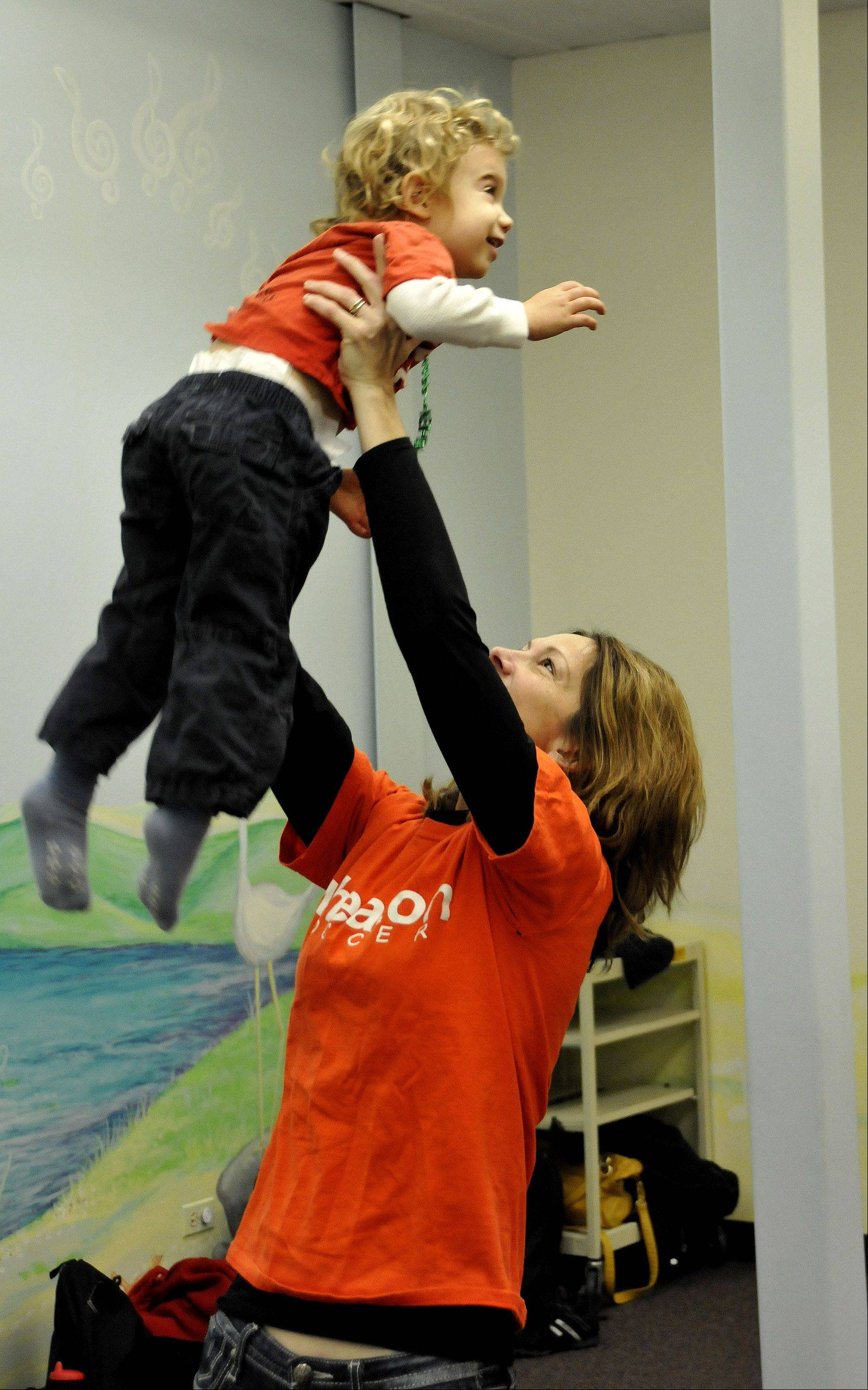 Jennifer Felske lifts Hayden Felske up during warm-ups at an early childhood music class.