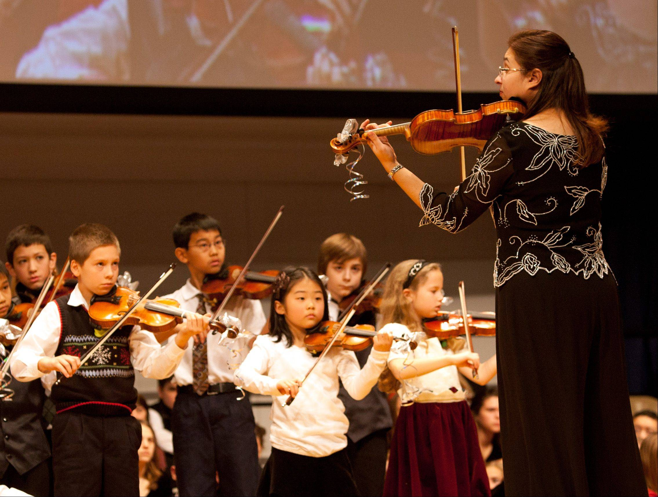 "Julie Bickel, chairman of the Christmas Concert Committee, leads part of the Suzuki Strings students during ""The Spirit of Christmas"" concert."