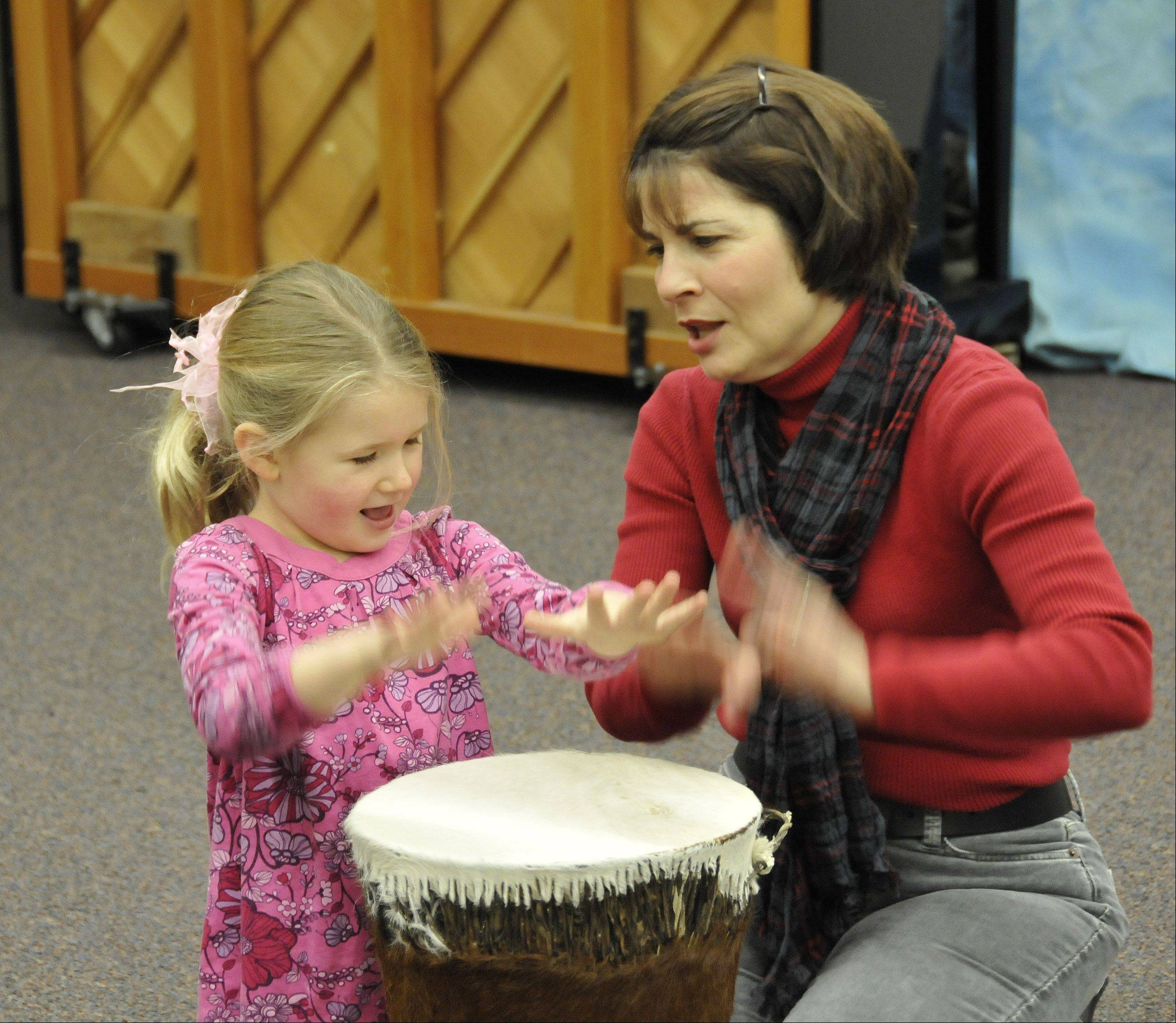 Music teacher Ann Storm plays the bongos with Adelyn Cathy before an early childhood music class starts at Wheaton College's Community School of the Arts. The school puts an emphasis on early exposure to the arts.