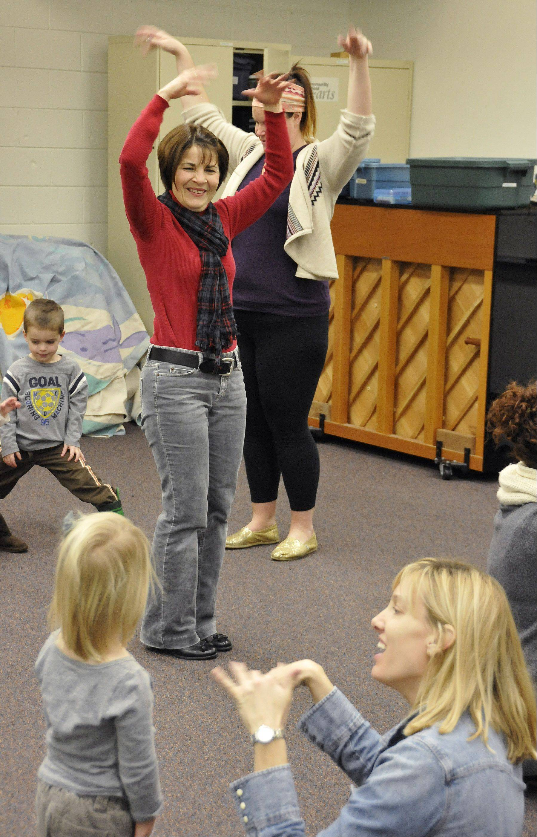 Ann Storm, in red sweater, teaches music to young children at Wheaton College's Community School of the Arts.