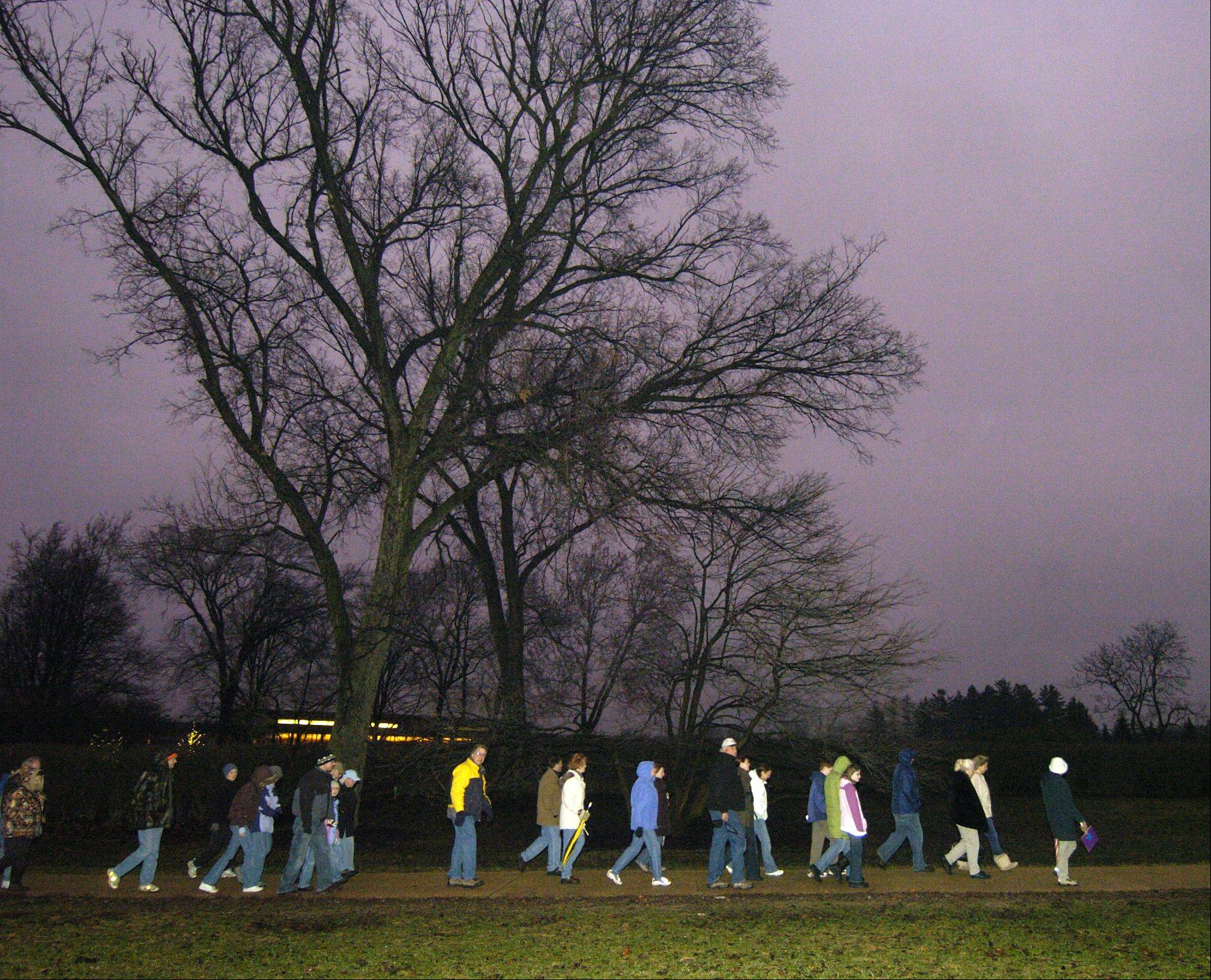 Participants during a previous winter solstice Walk make their way down the path at the Morton Arboretum in Lisle.