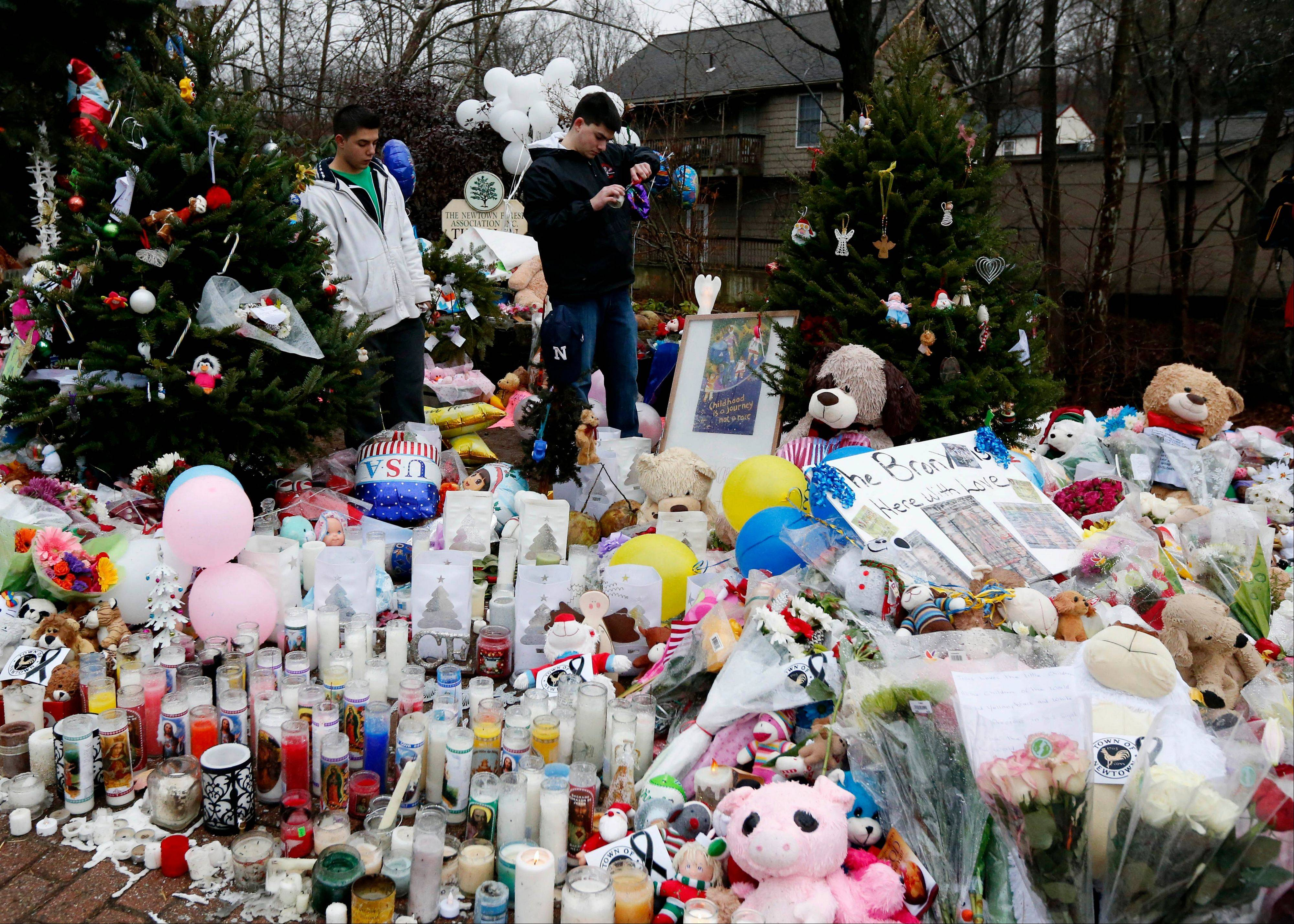Ryan Bartolotta, 17, right, and Ray Massi, 18, light candles that were put out by rain at a makeshift memorial in Newtown, Conn., as the town mourns victims killed at Sandy Hook Elementary School.
