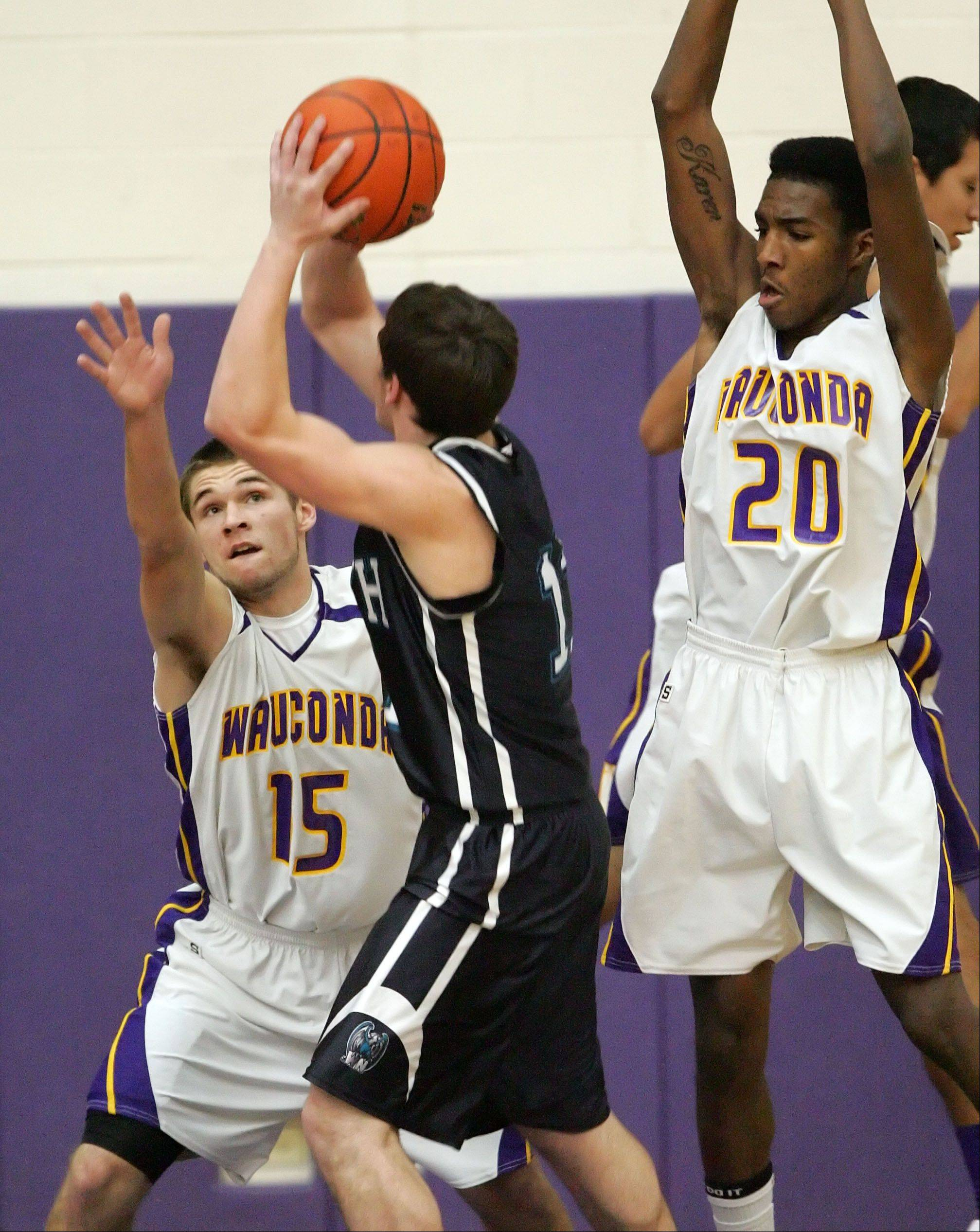 Wauconda's Keith Blomberg and Devon King defend against Woodstock North's Steven Whiting during their game Monday night in Wauconda.